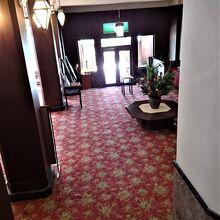 2階階段から重厚な入口ロビーを望む