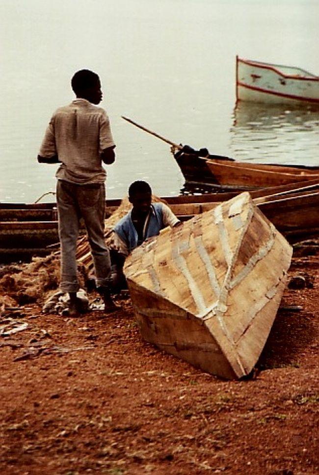 ★2017年8月:新たに出てきた画像をアップします。★ <br /><br /><br />この時は親戚がルワンダに滞在していたので、当時住んでいたドイツからケニア旅行を兼ねての訪問。<br /><br />ちょっとルワンダの歴史の復習。<br />ルワンダは62年7月にベルギー領から独立。<br />農耕民族のフツ族が多数派、牧畜民のツチ族が少数派という構造でも、その後の支配はツチ族中心に行われてきたらしい。<br />73年7月に多数派フツ族の軍事独裁政権が誕生。<br />90年には少数派のツチ族が組織するルワンダ愛国戦線が攻勢に転じた。<br />そのたびに優勢な側による弾圧・虐殺などがあり、内戦が繰り返されて来たとのこと。<br /><br />SUR SHANGHAIとその旦那がルワンダに行ったのは、94年に始まる内戦の前。<br />それでも親戚によって行動が規制された滞在でした。<br /><br /><br />ケニアの夜の山中でジープがエンストすると言うハプニングのあとはナイロビから飛び立つばかり。<br />SUR SHANGHAIとその旦那は「ルワンダって、首都キガリの空港に着いたあと、どうやって親戚のところに行くの?」なんて事を言っておりましたが…、そこには親戚がランドクルーザーでお出迎え。<br /><br />それを見た瞬間、イヤな予感。<br />SUR SHANGHAIたちは管理された旅はイヤなのに、この親戚は仕切りたがり屋。<br />それを忘れていた…。<br /><br />そして、ライフルを持ったガードマン付きの彼女の邸宅へ。<br />おお、ドアは防弾だ?!<br /><br />一息つくと、案の定彼女は命令を下しました。<br />「危険だから、この敷地外に出ちゃダメ! 一緒に外に行く時も勝手に私から離れちゃダメ! お土産が欲しかったら、私が連れて行く所で買うこと! スケジュールはもう出来てるからね!」などなど…。<br /><br />その晩、旦那とぼやく。「つまんないね?。」<br /><br />その後の数日はこの状態で、郊外の湖や密猟者に捕まったマウンテンゴリラを保護している施設を見学。<br /><br />一番印象に残ったのは、最終日。<br />「空港までの道に不穏な動きがある。」と、ボディガード付きのお車に乗せられました。<br />このおにいちゃんたちが映画に出てくるような黒背広のクールなタフガイ。<br />話し掛けるのも目を合わせるのもためらってしまうプロの雰囲気を全身にまとってる! <br />この手の研ぎ澄まされたオーラを見たのは初めてだったので、見惚れてしまったSUR SHANGHAIでした。<br /><br />上記の訪問からしばらく経ったある日、この親戚から「さっき大統領の乗った飛行機が撃墜されたらしい。しばらく連絡できないかも。」という94年の内戦の始まりを髣髴とさせる電話。<br /><br />その後、その親戚はそのまま内戦に巻き込まれてしまいましたが、結局はアメリカ軍のコンボイで隣国ブルンジに脱出。<br />その親戚も三児の母となり、2010年1月現在は日本にいます。<br /><br /><br />表紙の画像は、キガリ郊外の湖にて。<br />