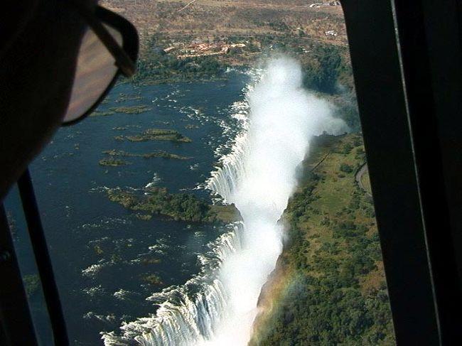 ビクトリアの滝はナイヤガラの滝、イグアスの滝と並び世界三大瀑布の一つ。世界遺産にも登録されている。英国人のデビット・リビングストンにより1855年発見された。アンゴラの奥地に水源を持つ。ジンバブエとザンビアの国境線にもなっている。ビクトリアフォルズと呼ばれているが、現地名は「モシ・オヤ・ツンヤ」といわれ「雷鳴の轟く水煙」という意味である。その名の通り水煙が凄い!風の向きによっては遊歩道は夕立の土砂降りの中を歩いているくらいである。最大滝幅1,700m、落差108mの規模を誇る。私の感じでは南米のイグアスの滝には及ばない。見る順序を間違えないように・・ <br /><br />詳細は<br />http://yoshiokan.5.pro.tok2.com/<br />旅いつまでも・・★画像 旅行記<br /><br />をご覧下さい。<br /><br /><br />本文は <br />http://yoshiokan.5.pro.tok2.com/nana/nori140nana.html<br />ジンバブエの旅をご覧下さい。