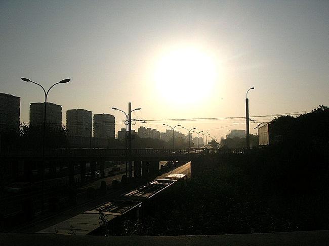 北京には12泊13日滞在しまして、12回朝を迎えましたが、8回早朝ジョギングをしました。<br />ジョギングと言いましても、私の場合は、体重が体重ですので、超スロー・125m/分という、はや歩きに毛の生えた程度の速度です。軽快には程遠く鈍重そのもののドタバタ走りですね。<br />北に真っ直ぐ行きバスで帰ってくる、あるいは西へ、東へ・・・とにかく真っ直ぐ行きバスで帰って来る、そういうジョギングです。大体、毎朝50分から60分走りました。北京は広々としていますので真っ直ぐ行ってもぶつかることはない。道自体も広々としていますし、7時ごろでも、上海に比べて、自転車も人も少ない、また上海ですと小さな脇道がたくさんあり、そこからバイクや自転車が突っ込んできたりするんですが、北京ではそういうことはない。上海ではここ数年早朝ジョギングはしてませんが、北京ですとジョギングしたくなります。<br />この日は、亜運村から南へ真っ直ぐ、安定門まで行ってきました。途中、元土城遺址公園により公園を散策、安定門まで行きましたら地壇公園を散策しました。<br />この散歩記録は安定門までの道の様子と元土城遺址公園の様子をアップします。<br /><br />表紙の写真は安定門から東の空を写したものです。8月15日、朝の6時34分です。