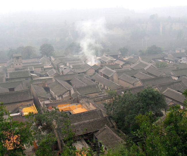 このあたりの10月11月は濃い霧が何日も続くらしいです。その濃い霧の中、10月6日に党家村に行ってきました。党家村は西安から東北に200kmぐらい行った所にある古い村で、670年も続く古い村だそうで、黄河の近くの黄土高原の中にあります。殆ど党氏と賈氏という人だけが住んで居るそうです。<br /><br />明、清の時代の四合院の形式の家が、125戸も昔のままの姿で残っている村です。いちばん新しい四合院でも100年以上も前の古い物だとか。昔この村が商業で栄えた頃に作られた四合院形式の家なので、北京の四合院などよりは作りが豪華なのだそうです(しかし面積は小さい)。豪華さは石や木や煉瓦にさまざまな彫り物が残されていることからも解ります。北京のものと違うのは、正面の奥の部屋が先祖を祭るところであったり、二階があったりするところも違います。党家村は「伝統的な民居の生きた化石」とも言われるところです。<br /><br />村の崖の上にもう一つの村があり、その村は城壁で囲まれていて、匪賊に襲われたときなどはこの村に逃げ込めるようになっていました。この村に行くには黄土を穿ったトンネルを通って行くのですが、その入り口には頑丈な城門がありました。<br /><br />なお、表紙の写真は村を崖の上から見たところですが、写真の黄色い部分はトウモロコシを干しているところです。屋根が平らなのは新しい家屋だと思います。<br /><br />