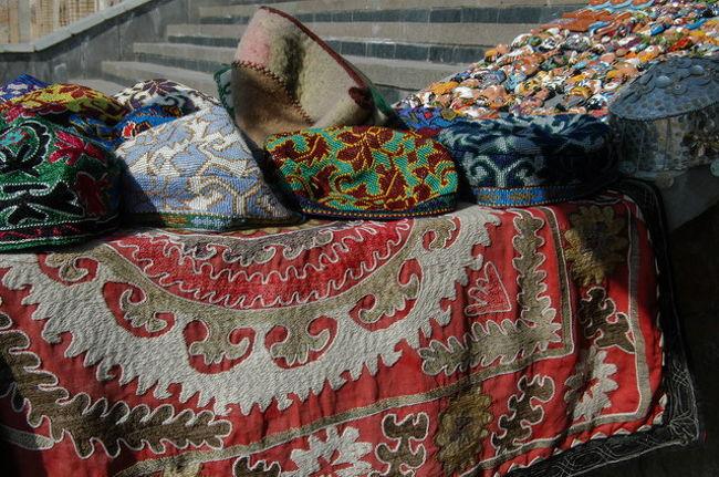 チムール廟の入り口横の土産物屋、10年前と変わらず。当時、店番をしていた少女は既に大人、聞いてみたところ姉妹だからどちらかだろうとのこと。1996年の写真(http://uz.iio.org.uk/samarkand.htm)<br /><br />写真はSUZANI、ウズベキスタンの家庭で作られている手作りの壁掛け、嫁入り道具の一つにもなっている。地方により特色があるようだ。最近は、土産用に増産され観光地で見かける。<br /><br />廟の階段が10年前は横から降りる階段だったが、正面から降りる階段に変わっていた。それでも階段横にあった土産物屋は当時と同じだ。