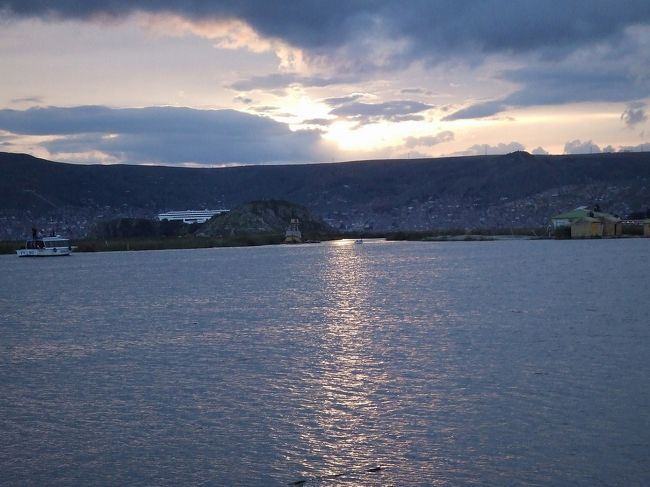 ウロス島の続き。奥に見えるのは、プーノの町。白い大きな建物は、チチカカ湖のエステヴェス島にあるリベルタドール(五星)ホテル。朝日と夕日が綺麗に見れる場所として有名。<br />プーノの観光名所<br />-プーノの目玉:ウロス島半日観光、午前と午後毎日出ています。<br />-他の観光名所:タキーレ島、アマンタニー島、シジュスタニ遺跡観光<br />-ボリビア国ラパス側:太陽の島、月の島、カラウタ島とスリキ島<br />-プーノからクスコヘ列車とバスで行けます<br />-ボリビア国のラパスにもバスでチチカカ湖を観光しながら行けます<br />