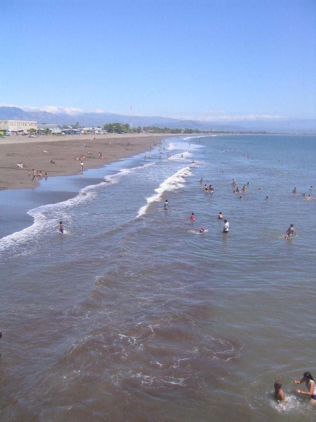 コスタリカの海の玄関口のプンタレナス (Puntarenas)<br /><br />そんなに 大きな街ではないけど、ビーチには 海水浴を楽しむ人で賑わっていた。ちょっとしたリゾート地のようだ。でも、今まで見てきた カリブ海の島々と違って 驚いたのが、茶色い砂!みんな泥だらけになってるし・・・。<br /><br />日本人のお客さんは こんな 汚そうな海には 入れないよ!なんて 言っていたけど、海の水は 実は綺麗なのかも?と思い、興味本位で 海に入ってみる。やっぱり 真っ黒、ドロドロになった(苦笑)<br /><br />ちなみに、プンタレナスは「砂の岬」という意味。5キロほども砂浜が海に とびだしたように続いていることから その名前がついたのだとか。<br /><br />とりあえず、腹ごしらえをしよう!と思い、ビーチのそばの露店をめぐる。道端では 何人も 同じようなサラダを売っている人いて、そのうちの1人の おばちゃんから サラダらしきものを購入。それが 安くて 旨い!!!おばちゃんに 何度も「おいしいよ!!!」と言ったら すごく 嬉しそうな顔をしてくれた。名前も 聞いたんだけど、忘れてしまった。後で、コスタリカ人の同僚 ジェイナに 説明したんだけど、名前はわからない、って。書き留めておけばよかった。悔やまれる。<br /><br />街の散策に出かける。小さな露店がいっぱい出ていて、アクセサリーなんかも すごく安い。お土産用のマグネットなんかも 他の場所より全然安い。熱帯気候のコスタリカにふさわしく、カラフルなものが多い。羽を拾うと幸せになるといわれている幻の鳥、ケツァルや、手押し車みたいなのが 有名なのか それをモチーフにしたものも多かった。<br /><br />それから、カフェのおじちゃんに頼んで、 アメリカドルとコスタリカの貨幣を 交換してもらった。いくらか よくわからないけど、カラフルなものと 真っ赤な紙幣、それから かわいい絵柄のコイン。これも 貴重なお土産。<br /><br />あたしが この露店めぐりを楽しんでいると、一人の男の人が からんでくる。最初は無視していたんだけど、しつこさに負け、結局、カタコトのスペイン語で 会話を続ける。ちょっと 酔っ払い気味のこのニカラグア人、ホセは バカンスで 遊びに来ているんだという。 なんだか 気がついたら あたしも ホセと意気投合。ホセはこの後、あたしの買い物にも 付き合ってくれて、あたしの名前入りネックレスを買って、プレゼントまでしてくれた。<br /><br />歩きつかれたので、ホセがお気に入りだという 近くのバーに立ち寄る。 地ビールを 飲んでいたんだけど、ホセは そのまま うたた寝をはじめてしまった・・・。普通寝るか?と思いつつも、ラテン民族だし、仕方ないか、と思うことにする。<br /><br />ホセが(寝てしまう前に)絵葉書を1枚買って、あたしに渡していた。「日本人の友達になんて なかなか 出会えるもんじゃない。この記念に、この絵ハガキを 僕のうちに 送ってくれ」って。なかなか かわいいこという人じゃないか。<br /><br />結局、その後 アメリカから送った 絵ハガキ。無事に ホセの家に届いたかな。