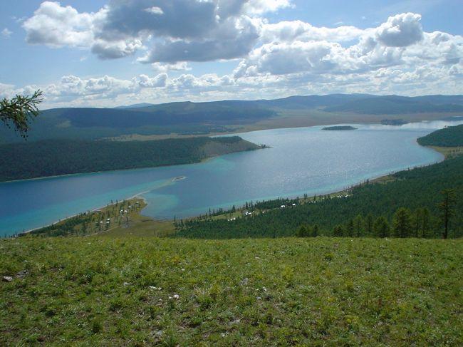 """モンゴルの北に世界で指折りに入る透明度がある大きな湖があると聞いた。<br />興味津津、湖の名前はフブスグル湖!ちょっと言いにくい感じ、聞き慣れない湖。<br /><br />ただ漠然と大きな湖といっても、イメージが湧いてこないので調べたところ、日本の琵琶湖の4倍ほどの大きさなんだって!湖というよりは海といったほうがふさわしいのかも。<br /><br />個人手配で行くことはあまり容易ではないのでツアーで行くことにした。<br />モンゴルは英語よりはロシア語のほうが通じる国、個人で現地と交渉して旅の手配をするには<br />なかなか至難な国だから。<br /><br />日本からのツアーは8日間。そのうちブスグル湖畔の滞在は3日間。<br /><br />モンゴルの首都ウランバートルより国内線で約1時間半のフライト。<br />フブスグル湖の玄関口であるムルンという人口約1万人の町に着いた。<br /><br />飛行機にタラップが掛けられ、一人ひとり降りる。さすがにモンゴルの北にあるだけあって<br />ウランバートルにくらべると少し空気がひんやり涼しい感じ。<br />日中になれば、気温も上がり、暑くなるかもね、とガイドさんは言っていた。<br /><br />空港のターミナルまでは滑走路を直に歩いて進む。機内に預けておいた荷物は飛行機から車で運んでくる。ターミナル内で荷物を受け取り、空港を後にする。<br /><br />空港から湖の湖畔にあるツーリストキャンプまで車で約1時間30分。<br />湖にたどり着くためには町を抜け、悪路を行かなければならなかった。それでも、悪路の試練に耐えてこそ湖に着いたときの喜びはひとしお。<br /><br />ロシア製のジープに約1時間30分ほど揺られながら一路、湖をめざす。<br />道路は舗装されていないため、ガタガタ。多少の揺れを我慢しないとならないけど、30分もすれば、その揺れが心地よく感じられ、いつの間にか、うとうと寝てしまう。<br /><br />車で約1時間を過ぎたあたりから、ふと気付くと、周りに小高い針葉樹の森林が見えてくる。<br />その森林が途切れた間から湖がちらちらと見え隠れする。そして。ついに大きな湖が姿を現した。車の窓越しに見たその湖は、まさしく海といっていいほど広く大きく感じられていた。<br /><br />みずの色は澄んで、とてもきれいな色をしている。岸際からエメラルドグリーン色がグーンと広がり、湖の沖のほうに離れるにつれてコバルトブルーへと色が変わって見える。湖と針葉樹に囲まれたこの風景はまさにスイスを連想させる。<br /><br /><br /><br />ツーリストキャンプへ向かう途中、湖のほとりに車を止め、湖に直に歩いて近づく。周りは、白い玉砂利のような石が広がる。太陽の日差しがこの白い砂利を反射してとてもまぶしかった。<br />湖は波がよせては返し、その広さに圧倒される。やっぱり海にしか見えない。<br />泳いでみたくなるような水の透明感の素晴らしさは""""フブスグル湖に来てよかったなぁ〜""""と心底思わせてくれた。せっかくのきれいな水にふれない手はないと思い、手を静かに入れてみる。""""ぎゃあ〜""""水は手が凍るほど冷たい!!泳ぐのはちょっと・・・。<br /><br />ツーリストキャンプへ到着!この湖の周辺にはいくつかキャンプ場がある。モンゴル特有のゲルという建物に泊まることができる。モンゴルにツーリストキャンプはたくさんあるようだけど、湖を目の前にしたキャンプ場はそうはお目にかかれない。オーシャンリゾートを思わせるツーリストキャンプ場はフブスグル湖畔だけかもしれない。<br /><br />このフブスグル湖滞在中の3日間はすべて自由行動。<br />できる限りのオプショナルツアーはすべてトライしないともったいないかも。<br />オプショナルの申し込みは夕食後、ガイドさんを通して申し込みができる。<br />翌日、可能なオプショナルツアーや時間などを案内してくれる。<br /><br /><br />湖での1日が終わり、フブスグル湖畔に夜が訪れると静かな暗闇に包まれる。そして、煌めく星々が夜空を彩り、夜空は星屑のステージ。<br />天の川がまるで天女の羽衣のようにたおやかに流れ、いくつもの流れ星は弧を描き星空から消えていく。人工衛星が一定の速度をたもち、ゆっくりと進むさまはまるで望遠鏡を使わずに宇宙空間を少しだけ覗いているような気持ちになれる。<br /><br />この3日間で参加できたオプショナルツアーについて<br /><br />その1針葉樹の林をピクニック<br />針葉樹の森林を現地森林ガイドさんの案内でピクニック。<br"""