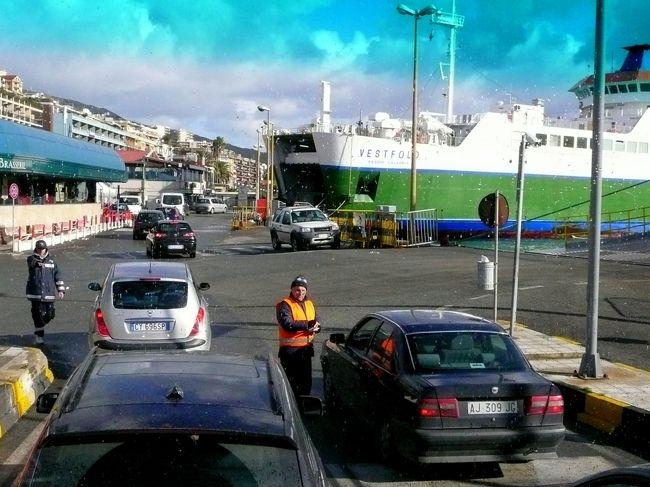道路はメッシーナ湾に直角に伸びており、海の中に、航行の安全を祈願して建てられたと云う海のマドンナ像を頂く高い塔が、バスの窓にまっ先に飛び込んできた。<br /><br />海岸の道路沿いに桟橋に向かう。<br /><br />たまたま雲が切れ、強い日差しに映った、車の乗船が始まる桟橋の光景は、明るく活気に満ちていた。<br />