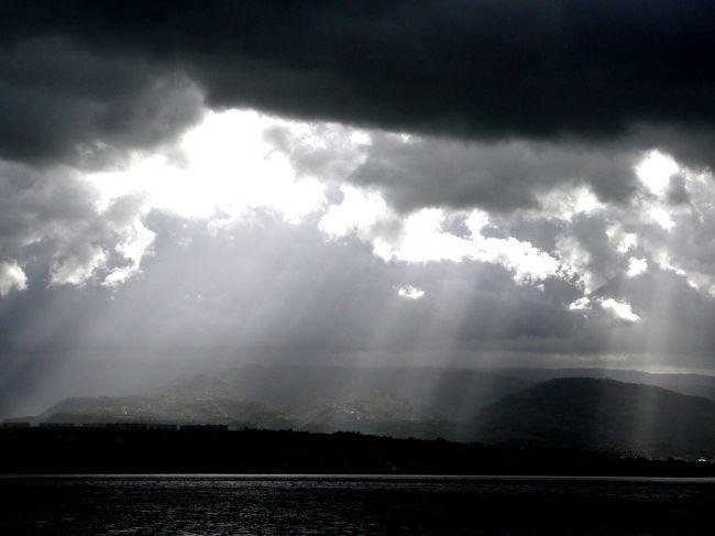 """メッシーナ海峡はシチリア島のメッシーナとイタリア本土のヴィッラ・サン・ジョヴァンニを結ぶ、距離約3km、航行時間30分の狭い海峡。<br /><br />乗船した時は、紺碧の海と空、空にはに夏の雲を思わせるような白い雲、何処か常夏の海岸風景。<br /><br />しかしその雲が次第に空いっぱいに広がり、ネズミ色から濃い藍色に変わり、まだ白さが残る雲間から、後光のように太い直線状の白線が扇状に広がって、地上に、海面に突き刺さる。<br /><br />その薄明かりの光が、スポットライトのように地上を照らし、黒ずんだ街影をその部分だけボンヤリ浮き上がらせていく。<br /><br />雲間の変化と、船の動きでその情景は瞬時に、次々と変化する幻想的な光景に、暫し時の経つのを忘れていた。<br /><br />気がつくと目の前にヴィッラ・サン・ジョヴァンニ港がの逼っていた。<br /><br />印象深かったシチリア島さらば!<br /><br />これで""""ssiシチリア島&南イタリア周遊旅情・A前編シチリア島""""は終りです。"""