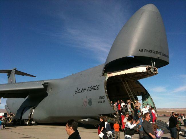 """アメリカでは11月11日がVETERAN'Sデー(復員軍人の日)で祝日となっていますが、ラスベガス郊外にあるネリス空軍基地(車で約30分)では毎年この時期に合わせ11月13、14日の2日間、航空ショーが開催されています。<br />I-15号線を北へ移動し、""""MOTOR SPEEDWAY""""の出口をおりるとレース場の大きな駐車場があります。(当日は多数のポリスが交通整理を行っています。)<br />まずはBLUE LOTというスペースに車を駐車し、そこからは専用シャトルバスで基地へ移動します。(一般車の進入不可)シャトルバスへ乗る前にまずは空港さながらの手荷物検査があり、クーラーボックスや大きな荷物の持ち込みは不可ですが折りたたみ式のイスなどは基地内にベンチなど座れる場所が殆ど無いので持ち込んでおくと便利です。<br />シャトルバスは数十台(いや、100台近く走っているのかな?)周っているので乗り場に100人位並んでいても""""往路は""""あまり待たずに乗車する事が出来ます。<br />基地に到着すると、敷地内には年代の古いものから最新のヘリコプターまで様々な機材が展示してあります。<br />ちなみにシャトルバス、入場料は無料です。<br />また、ハンバーガー、ホットドッグ、レモネード、そしてTシャツなどの空軍グッズなど屋台のお店も沢山並んでいます。<br />9:00AMに入場開始となり1日中T-33、B-25、F-22A、F-16などが飛行デモンストレーションなどを行っていますが、大トリ(メイン)は2:00PMから登場する""""Thunderbirds(サンダーバード)""""のアクロバット飛行です。<br />まずは滑走路に登場し、2:30PM〜3:15PMまで約45分間4〜5機での鍛錬された飛行技術を披露します。<br />その後パイロットによるサイン会の様な企画があって4:00PMにイベントが終了。<br />サンダーバードの飛行終了前あたりから、混雑を避ける為徐々に人々が帰り始めますが、<br />3:30PM〜4:00PMあたりは""""復路""""のシャトルバスが大混雑します。<br />11月とはいえ晴れの日は陽射しも強く、また上空を見上げているので日焼け止め、サングラスは必需品、また設置されているスタンドの席数も極めて少なく、ハンバーガーなどを買い食いする際に座る様なベンチも無いので、折りたたみ式のイスもあると便利です。(現地でも購入可)左右上下と行き交う飛行機のジェット音もかなりのものなので耳栓もアリでしょう。<br />普段は一般人が立ち入り出来ない米軍基地内での、またイベントを手伝っている現役軍人とコミュニケーションが交わせる貴重な体験です。<br /><br />黒澤/クロスインターナショナル<br />www.kurosnavi.com<br /><br /><br /><br />"""