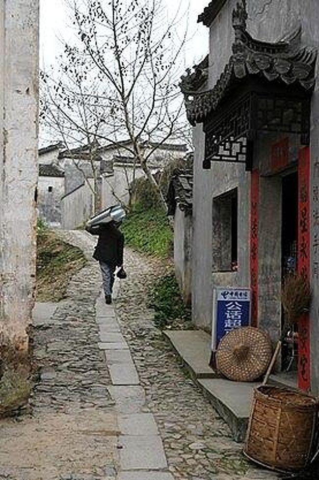 2002年に初めて安徽省の古村群を訪れた時には、友人たちの車で真っ先にこの南屏を訪れた。<br />映画『菊豆』の舞台になったこの村には、ロケ中の鞏俐(コン・リー)が泊まっていたという民家が菊豆飯店になっていて、そこで晩ご飯を食べたんだよね。<br /><br />あれもちょうど春先だったし、ちょうど8年振りの再訪。<br />あの時と同じように、今にも雨が降り出しそうな空模様。<br />でも、今回のSUR SHANGHAIは、一人でこの村をさまよってみます。<br /><br />南屏は、宏村と同じく安徽省黄山市[黒多]県にある小さい村。<br />ここも皖南(安徽省南部)の独特の風格を持つ民家が美しい所で、鞏俐(コン・リー)主演の映画『菊豆』で有名になりました。<br />●注: 日本では、県の中に市がありますが、中国では逆。市の中に県があります。<br /><br />表紙の画像は、南屏の村の小道