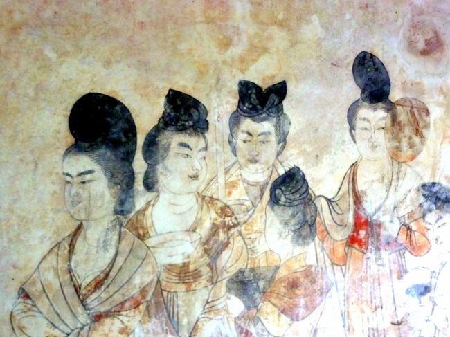 広大な「乾陵」には陪塚が17もあり、「永泰公主墓 」もその一つ。<br />「永泰公主墓 」は乾陵博物館と同じ敷内に隣接している。<br /><br />墓の主は永泰公主、本名李仙、皇帝高宗李治と皇后則天武后の孫、息子中宗の第七皇女である。<br /><br />公主の死因は棺には難産と書かれているが、実際は皇帝になった則天武后が、武后の若いそばめの兄弟に一切を任せる政務のやり方を、公主が夫共々批判していたため、武后の怒りに触れて二人共殴り殺されたと云うことらしい。<br /><br />公主はまだ17才の若い妻女であったし、公主の夫は武后の親戚筋の者であった。<br /><br />最初公主は洛陽に葬られていたが、則天武后の死後、父中宗は洛陽にあった娘の墓を乾陵の近くのこの地に移し葬った。<br /><br />墓は土を盛って造られ、玄室迄87.5mのトンネル状のスロープが有り、トンネルの壁には白虎や青龍、高松塚古墳の壁画のモデルと云われる唐の女官や官吏達が描かれており、女官達の艶っぽい美しさに目を奪われる。<br />(ガイドさんに頼んで、NOフラッシュで壁画を撮る許可を得た。)<br /><br /><br />「乾陵博物館」には「永泰公主墓 」を中心に、乾陵の陪塚から発掘された出土品が時代毎に分類されて展示されている。<br />西域の人の姿の埴輪が多く見られ、この時代シルクロードとの交流の深さが感じられた。<br /><br />「唐高宗与則天武后皇帝合葬之墓」で時間を喰った為、乾陵博物館は流し気味の見学。<br />