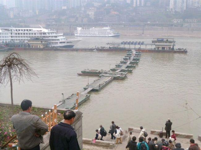 <br />2011年3月11日(金)<br /><br />ぐっすり寝て、目が覚めたのはモーニングコール5分前の5時25分だった。<br /><br />窓からの景色が楽しみで、カーテンを開けてみたのだが、まだ重慶の朝は明け切れていなかった。<br /><br />本日は重慶の港から「長江一号」に乗り、9泊10日で上海への川下りの旅が始まる。<br /><br /><br />港までバス。<br /><br />車窓から見ると、坂やカーブの多い街だ。<br /><br />この街の都市公共鉄道は三線出来ているが、その内二線がカーブと坂に強いゴムタイヤ・モノレールである。<br /><br />日本のODAで、私の友人たちが設計した。<br /><br /><br />港を見下ろす展望台で、バスを降りる。<br /><br />「あぁ、これが音に聞く長江なのだ!」<br /><br />自ずから胸のときめきを感じる。<br /><br /><br />階段をずっと下って行き、河岸から浮橋を辿りながら浮き桟橋に係留されている船に至る。<br /><br />そのかなりの道のりを、親切な中国の男が腕を組んでくれる。<br /><br />スタートはやや無理強いのように感じたが、私の歩調を速めるために必要と考えなおし、腕を預ける。<br /><br /><br />最初のうちは抵抗を感じたが、歩くにしたがって呼吸が合い、次第にチームワークが生まれる。<br /><br />途中土産物売りがたくさんいるが、一番面白そうなのが、連凧だった。<br /><br />二十〜三十つないだのが、楽しそうに空を舞っている。<br /><br />売り子のおばさんに10元わたしたら、三袋くれた。<br /><br />一袋に、ひし形で、一辺が約十センチ角の凧が三つ入っている。<br /><br /><br />「長江壱号」が繋がれているポンツーンでは、赤金二匹の獅子が、銅鑼と太鼓で踊っている。<br /><br />船の出発祝いだろうか。<br /><br />それを聞きながら、ウキウキした気持になり、ポンツーンに足を掛けたところで、腕を組んでくれていた男はそっと放してくれる。<br /><br /><br />私は心から謝辞を述べて、とは言っても「シェー、シェー」しか知らないが、10元を渡すと、男は嬉しそうに拝みながら受け取った。<br /><br />ここまで、中国との出会いは、期待を大きく超える、素晴らしいものだった。<br /><br /><br />写真は「ソフィさんの旅行記」http://4travel.jp/traveler/katase/をご覧ください。<br /><br />「片瀬貴文の記録」http://blog.alc.co.jp/d/2001114もご訪問下さい。<br /><br /><br />(2011.3.30 片瀬貴文)<br />