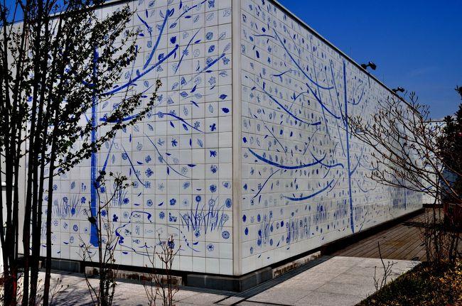 """<br />   博多駅の """"アートプロジェクト""""・・・タイル画見学<br /><br /> 昨年3月に九州新幹線が全線開通、早くもあれから1年経過した。この全線開通に伴い、JR九州の拠点でもある""""博多駅""""がリニューアルオープンされたことは、地元の皆さんならよく知っている。<br /><br /> この開業に合わせて、JR九州は""""タイル画アートプロジェクト""""をスタートさせたことはあまり知られていないと思うので紹介させて頂くことにしましょう。<br /><br /> """"タイル画アートプロジェクト""""というのは、博多駅をリニューアル(改装)する際に駅の構内や屋上に一般から応募した、葉っぱや花・鳥・魚などの絵を""""有田焼""""にして、その""""タイル画""""を駅構内あらゆる場所に貼り巡らそうという計画のことなのです。<br /><br /> そのためにJR九州の各駅にポスターを張ったり、チラシなどを配布したり、鉄道誌・フリーペーパー・旅行誌などを使って大々的に広報活動を行ったという経緯があるんですな。<br /><br /><br /> 「応募作品は、有田焼のタイルに・・」<br /><br /> そうして集まった作品を転写紙に写し、それを""""有田焼""""のタイルに貼り、釜入れ・釜焼きをしてタイル画が出来上がり、その出来上がったタイル画を、千住先生や水戸岡先生が丁寧に一枚ずつ敷き並べ検査を行い、確認作業をしてようやく出来上がるんです。<br /><br /> そうした手間暇のかかる作業を終えた後、JR博多駅のあらゆるところ(博多シティの吹き抜け、中央コンコース、通路、屋上など)に有田焼のタイルが貼られて""""タイル画アートプロジェクト""""が昨年の春、JR九州新幹線開通に合わせ、完成・公開されたのです。<br /><br />  第一回の応募イベントから足掛け3年、ようやく博多駅に""""アートプロジェクト""""が完成、それから1年経った今年・2012年、ようやく実際に自分の目で""""タイル画""""を確かめることができたのです。<br /><br /> というのは、このタイル画に山口在住のうちの孫が応募しているのです。このような企画があることを当時、小三の孫に教えたところ即、これに応募しましてね、<br /><br /> テーマは「葉」でしたが、20cm平方の台紙にクローバの「葉」を書き、千円の参加費(協力金)を支払い事務局に送付したという経緯があるのものですから・・・。<br /><br /> 広島から福岡・博多まで都市間高速バスで4時間。博多に到着。JR博多駅で孫の応募作品を探すことにしました。<br /><br /> あらかじめ、作品が展示されている位置はどこなのかネット検索すればすぐにわかるようになっているので探すのに苦労はありません。<br /><br /> 作品の展示位置は、屋上""""つばめの杜ひろば""""、天空の広場の一角にありましたが、そこだけでなく、博多駅コンコースのいたるところに、""""アートプロジェクト""""の作品が展示されているのには驚きでした。ここにも、あそこにもあらゆる所に""""タイル画""""が貼られているではありませんか・・・。<br /><br /><br /> 「応募者總数は2万8千枚も!!」<br /><br /> それもそのはず、JR九州の""""アートプロジェクト""""のHPを見たら、28、525枚もの応募作品があったそうですから・・。総額にして2千6百万円の参加費が集まったそうです。<br /><br /> さらにHPを見てみると、日本国内だけでなく中国や韓国、タイ、マレーシアなどから2000枚もの応募があったそうですから、この企画は大成功と言えるでしょう。<br /><br /> という訳で、JR博多駅に展示されている""""タイル画""""を見学するという目的だけのために、博多へ行ってきました。<br /><br /><br /><br />   JR博多駅""""アート計画""""のページをご覧あれ!!<br /><br /> 内容・・タイル画配置イメージ、募集について、千住さん、水戸岡さんの紹介、タイル画アートができるまで <br /><br />   http://www.jrkyushu.co.jp/touban/art.html<br /><br />   http://www.hakata-artproject.jp/ja<br /><br /><br />"""