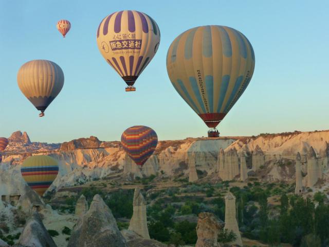 翌々日は先ず熱気球ツアー!から始まります。<br />早朝気流の安定した時間に離陸します。<br />気球ツアーのツアー会社は沢山ありますが、パイロットの技量の判断は大事であるという事が良く判りました。<br />見ているとヘタクソなパイロットは最初からドンドン上に上がって行って、そこらでポカーッと浮かんでいるだけです。我々のパイロットは仲間と高度による風向きの違いをハンディトーキーで連絡し合いながら上がったり降りたり、キノコ岩の林や樹木すれすれに飛んだりしてくれました。<br />今回予約したのはVoyager Balloonsでした。<br /><br />気球を上昇させる為にバーナーをゴーッ!と燃やす音は凄いです。<br /><br />音と動画は<br /> https://www.youtube.com/watch?v=Yiu_d21LK0o&amp;feature=youtu.be<br />でどうぞ!