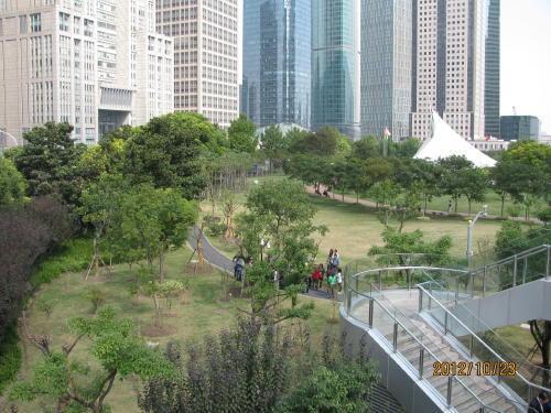 中央緑地は1997年7月オープン、面積10万?、「城市緑化」を目的。発展目覚ましい高層ビルが林立する陸家嘴の真ん中にあるオアシスが中央緑地。白玉蘭、銀杏、雪松など四季常緑で埋まり、浦東新区の形状の中心湖を配置し、湖には日本から来た錦鯉が泳いでいる。<br />最高50mの噴水、池の畔の観景篷は白い海蝶のようです。観景篷には休憩、飲料、軽食、展望などが楽しめます。<br />百年欅など樹木も豊富。芝生の中を曲がりくねった遊歩道にはベンチがあり、昼下がりには周りのビルから多くの人々が出て、食事や読書や休憩にと公園を利用しています。園内の一番南側には陸家嘴開発陳列館がある。<br />夏季開放時間6時〜22時、冬期7時〜21時。入場無料。<br />