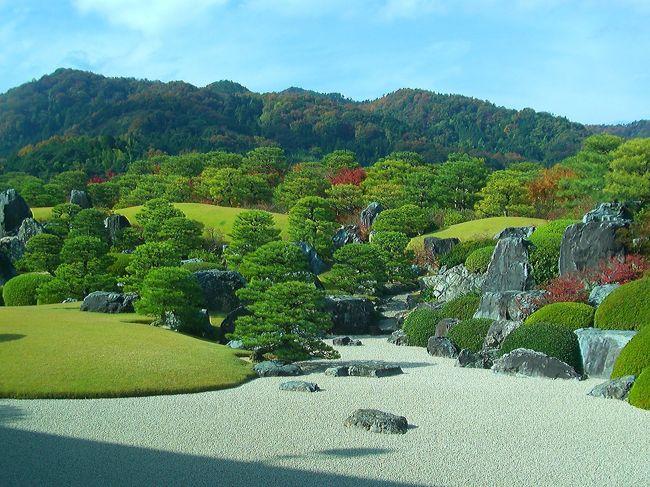 同日の11月21日の朝刊によりますとアメリカの日本庭園専門誌「ジャーナル・オブ・ジャパニーズ・ガーデニング」の日本庭園ランキングで横山大観のコレクションで知られる足立美術館が見事日本一に選ばれ、これで2003年から続けている日本一の称号を10年連続に延ばすと言う快挙を成し遂げました。<br />(ちなみに前作の由志園は38位だとかで、それでも全国900庭園の中からですので立派なものです。)<br /><br /><br />またフランスの旅行ガイド『ミシュラン・グリーンガイド・ジャポン』や『ギッド・ブルー・ジャポン(ブルーガイド)』でも山陰地方では唯一の「三つ星」を獲得、高い評価を受けています。<br /><br />広さ約16万5000㎡(約5万坪)の園内には枯れ山水庭や苔庭など6つの庭があり、手入れの行き届いたアカマツ(約800本)やクロマツ、モミジ、ツツジ、サツキなどが専門庭師(5人)によって植栽、手入れをされています。<br /><br />借景との自然と調和のとれた枯れ山水庭など、特に色の変わるこの時期は見ごたえがありますね。<br /><br />創設者、足立全康氏は農家に生まれましたが、貧しい農家を離れ若くして自ら商いの道へと進み木炭の運搬、販売を始めたのをきっかけにその後、繊維や不動産等色んな事業を興して儲けた資金で日本画等美術品を蒐集しました。<br /><br />その後、昭和45年に美術館を創設。<br />その美術館を世界の美術館にしたいと言う思いから美へのこだわりは庭へと続き自らが納得できる庭をと月日をかけて庭師に造らせたと言われています。<br /><br />●足立美術館<br /><br />○開館時間 <br />04月~9月 9:00~17:30 年中無休 <br />10月~3月 9:00~17:00 <br /> <br /> <br />※新館のみ、展示替え期間中はお休みをいただきます。<br />くわしくは[展覧会のご案内>2012年度 新館]ページをご覧ください。 <br /> <br />○入館料(税込) <br />①個人  <br />大 人    2200円 ¥1,800 ¥1.600 <br />大学生    1700円 ¥1,400 ¥1,200 <br />高校生*1    900円 ¥700 ¥600 <br />小・中学生*1*2 400円 ¥300 ¥200 <br /><br />②団体(20名以上)   ③団体(100名以上) <br />大 人    1800円     1600円<br />大学生    1400円     1200円<br />高校生*1    700円      600円<br />小・中学生*1*2 300円      200円<br /><br />※青少年の優遇処置について <br />*1公立学校が休業日となる土曜日は、小中高生の入館料を無料といたします。(要学生証提示) <br />*2小中学校(高校は含まず)の学校教育の一環として教師等が引率し利用する場合は、事前に申込みがあった場合に限り無料といたします。 <br /> <br />※音声ガイド <br /> 庭園の見どころと展示作品の解説を、音声で案内します。 <br /> 貸出料:1台 500円 受付で貸出。 <br />※駐車場 <br /> 大型バス40台、マイカー400台が無料で駐車していただけます。 <br /><br />