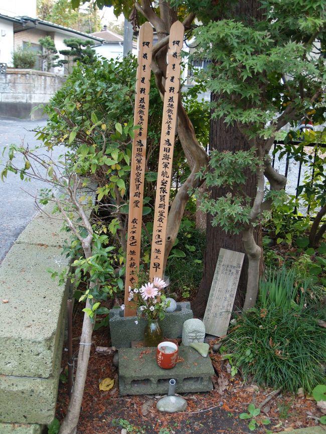 横浜市金沢区にある称名寺市民の森から下りてくると、称名寺仁王門の右脇に出る。称名寺仁王門脇に新しい2つの卒塔婆が立てられて戦死者の墓のようなものがあるのだが、石塔などは何もない。これまで、国内を巡っても戦死者の墓に石塔が建てられていないことなど1度もなかった。その前の家で尋ねてみた。<br /> 昭和18年(1943年)5月1日に群馬の飛行場から荷物を運んで戻ってきた99式艦上爆撃機に追浜飛行場(現日産追浜工場)から着陸許可が下りずに上空を旋回していたが、燃料切れになり、海までは遠いので称名寺横の畑(現在は空き地で草原になっている)に着陸しようとしたが、そこには畑仕事の人影が見え、躊躇しているうちに、仁王門の右脇の木に引っ掛かり、墜落し、パイロットら2人の搭乗員は亡くなられたのだという。何と痛ましいことであろうか。<br /> その後、亡くなられた2人の身元も判明し、墜落した命日にはこの家のおじいさんが称名寺のお坊さんを呼んで毎年供養していて、このおじいさんが亡くなった後もこの家の家族が引き継いで供養しているのだという。それで石塔が建っていないことに納得できた。2人の搭乗員のうち、1人は田舎に墓(石塔)が建てられ、遺族が墜落地のこの地にも訪れ、供養してくれていることに感謝し、お礼を述べに来られるという。もう1人は遺族がおられなく、墓は地元の人たちが建て弔ったようだとも言われている。<br /> なお、99式艦上爆撃機とは皇紀2599年(昭和14年(1939年))に制式採用された海軍の艦上爆撃機(空母から発着艦する)で、真珠湾攻撃などで活躍した。車輪が格納できないタイプでいかにも旧式な感じがする。翌、皇紀2600年(昭和15年(1940年))に制式採用された海軍の零式艦上戦闘機(零戦)は1人乗りで、離陸後には車輪が機体に格納された。こちらは、私のように、小学生の頃の漫画雑誌の特集は連合艦隊の艦船や戦闘機などばかりで、それを読んで育った世代でなくても、誰もが知っている名前であろうか。<br />(表紙写真は墜落現場跡の供養)