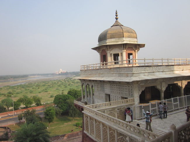 16世紀から19世紀にかけてインドを支配した、ムガール帝国の栄光と権力を象徴する城塞<br />ムガール帝国の歴代皇帝の中で唯一「大帝」と呼ばれたと言う第三代アクバル皇帝により、1565年建築開始<br />彼は、インドの南端(て何処だ?)を除くすべて全域を平定した人物でも有るようだ。<br />彼の死後も、タージマハルを作った第5皇帝、シャー・ジャハーン皇帝によって建築が続けられ、18世紀当初までかかってほぼ全域が作られたようです。<br /><br />この写真左中央に見えるのが、タージ・マハルです。