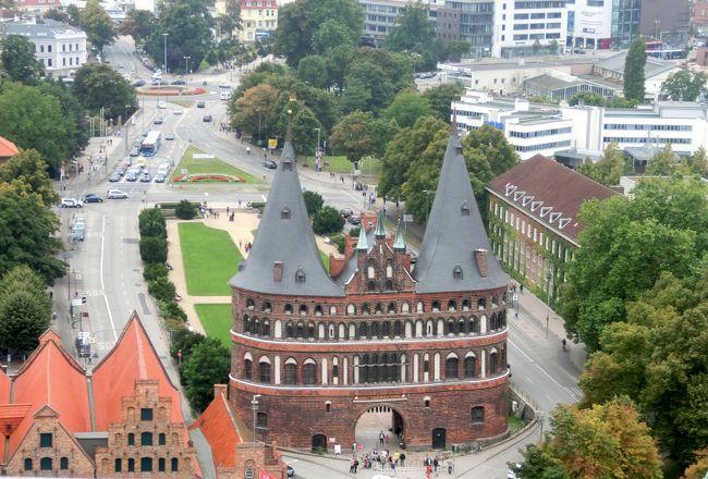 8/29(金)、10日目。<br /><br />今日はハンブルクから日帰りでリューベックです。<br /><br />ハンブルクの北東65キロ、人口22万の町。かってハンザ同盟の時代にはハンザの女王、バルト海の女王と言われました。<br />12世紀中頃、ザクセン・バイエルン大公ハインリヒ獅子公が建設しました。ハインリヒ獅子公は商業都市建設に積極的で、ミュンヘン、ブラウンシュヴァイク、リューネブルクなどもその建設になります。いわば領主の保護、お墨付きの町として発展したのです。<br />1226年にはフリードリヒ2世により帝国自由都市の特権を与えられました。<br /><br />リューベックがなぜハンザ同盟の盟主になったか。いろいろ理由を寄せ集めると、北海からバルト海に連なる商業都市のなかでで地理的にほぼその真ん中にある。ハンザ同盟以前からリューベックはヴィスマール、ロストックとかハンブルクなどと交易の安全を目的とした協定を結んでいた。ハンザ同盟の最大の脅威だった対デンマーク戦争でリューベックはその中心となって戦った。当時白い黄金と呼ばれた塩がリューネブルクよりリューベックに運ばれ、集積地であった、等々ではないかと考えます。リューベックからの移民によりロストック、ヴィスマール、シュトラールズントの街も造られています。<br /><br />13~15世紀にかけ全盛期を誇るが新大陸の発見、大航海時代の到来による商圏の変動、30年戦争による疲弊などでハンザ同盟は終焉を迎えます。<br /><br />当時の隆盛は無いもののリューベックは今でも重要な港湾都市であり、ハンザ同盟の面影を求めて観光客が数多く訪れる町です。<br /><br />写真は聖ペトリ教会の上からのホルステン門。