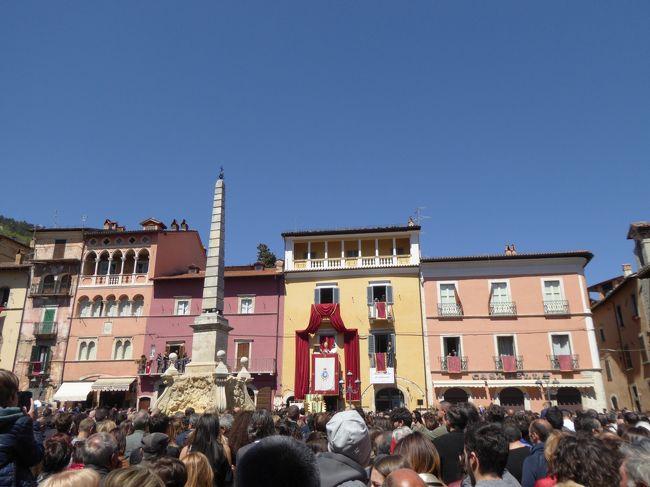 4月22日-5月5日の12泊14日、中部イタリアへ行きました♪<br />ラツィオ州・アブルッツォ州・モリーゼ州・カンパニア州を周遊。<br />観光・グルメ・温泉をたっぷりと楽しんできました♪<br /><br />☆Vol15:第2日目(4月23日)ターリアコッツォ♪<br />コッラルト・サビーノから専用車ベンツで40分ほどターリアコッツォに到着♪<br />アブルッツォ州に最初の記念すべき町。<br />ターリアコッツォは規模の大きな町で、<br />イタリア美しき村に選ばれている。<br />標高は750メートルで高原にある。<br />旧市街近くの新市街に車を停めようとするが<br />満車でしかも大渋滞。<br />何かイベントでもあるの?<br />やっと空きを見つけて専用車ベンツを停める。<br />停めた場所は旧市街への入り口にあたるPiazza Ducaleで、<br />そこから歩く。<br />旧市街への城門は立派で驚く。<br />城門はPorta del Marsiで15世紀のもの。<br />抜けるとカラフルな街並みに驚く。<br />中世時代のセピア色かなと思っていたので。<br />最初の広場に出てくるのがPiazza Argoli。<br />こからすでに群衆でいっぱい。<br />その隣接するように中心広場であるPiazza dell&#39;Obelisco。<br />その名から分かるようにオベリスクが建つ広場。<br />その周囲は壮麗な建物で囲まれ、華やいだ雰囲気。<br />でも、今日は群衆で埋め尽くされびっくり。<br />その一角にある建物のバルコニーでは牧師がお祈りをしながら説教している。<br />群衆は花を模った手作り物を手に持って真剣に聞いている。<br />訊くとお祭りで「Festa del Volto Santo」のこと。<br />春を告げる祭りだと。<br />あ~、なるほど。春の訪れを祝う祭りなのね。<br />その様子を見ながら、<br />周囲の風景を眺めて♪<br />