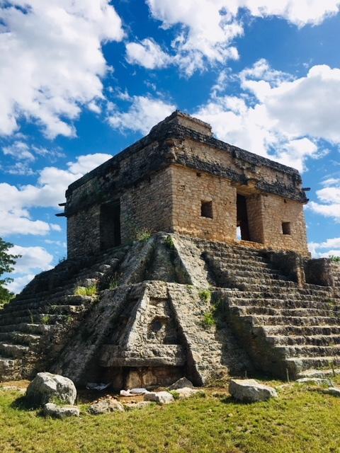 新しく開始したプウク・ウシュマル遺跡ツアーの関係でボクは今メリダに来ている。マヤ文明と一口に言っても文明の軌跡とは教科書で習ったように単純ではない。一つの文明の中にある一つのエリアの、更にその一つの都市の中の一つの建物といった部分にまで歴史というものが息づいているからだ。当然、その分歴史というものは複雑に絡み合い、単純にこの時代は誰それが統治し、その時代はどのような時代だったか。。。という教科書的な解説で済んでしまうようなものでもない。<br /><br />また、マヤ文明にはまだまだ解明されていない謎が多くある。ガイドをしているとそんな謎に数多く出会う事になるのだが、その中でも今回出かけたジビルチャルトンはかなりのロマンを秘めている。<br /><br />メリダから北へ20分ほどいった、昔からメリダ市民の避暑地としても有名なプログレッソへ向かう途中にある紀元前325年のマヤ先古典期からスペイン侵攻がある1542年まで、更にその後もフランシスコ・デ・モンテホがメリダに都市建設を開始するまで、スペイン・カトリックの布教と都市の拠点が1610年までおかれた実に2000年近くにわたって続いた息の長いマヤ遺跡。<br /><br />ここには15年ほど前に一度訪れた事があり、当時はまだ修復や発掘などがあまり進んでおらず見学できるエリアも限られていたことから単なる地方の小さなマヤの都市程度にしか考えていなかった。もちろん、当時から太陽の運行や儀式のセンターたるべく、マヤ文明北部低地のエリアではもっとも古い都市として注目されているという程度の事は分かっていたのだが、それ以上の文献にもそれ以前に発掘そのものが進んでいなかったこともあり、単なる見学で終わってしまっていた。<br /><br />ここ数年マヤエリアでは新たな発掘やマヤ碑文の解読などが飛躍的に進んでおり、この15年ぶりに訪れるユカタン半島最古のセンターに訪れるのを、だからこそ楽しみにしてもいた。<br /><br />因みに、新しい遺跡ではボクは必ずガイドを雇う。ボク自身がマヤ遺跡のガイドであり、正直その辺にいるガイドよりもさらに深い知識と見分を持っていると自負していても、やはりボクの知らない最新の発掘状況やセトルメントパターンという一般住居址にいたる都市の構成などの細かな情報についてはかなり参考になるからでもある。<br /><br />当然、いい加減なガイドも多くいるので、現地ガイドを雇う際にはボクは必ずどの程度の知識があり、ボク自身が求める情報をどの程度持ち合わせているのか確認を取る。一般の観光客向けの単なる見学の解説であれば不要だという事が向こうも分かるから当然緊張もしながら案内をしてくれることになるのだが、これがまたお互いに良い刺激を生み出してくれることも多い。<br /><br />何よりマヤ文明を愛して遺跡の案内を生業としているガイドに出会うと話も盛り上がるのもウレシイ。<br /><br />今回僕を担当してくれたMEMOは単なる教科書的な解説に終始することなく、彼自身がガイドを続けている中で発見した様々なこのジビルチャルトンという遺跡の謎とその解釈について語ってくれた。考古学者が出した結論も出された当時と今ではかなり違っている事も多く、特にここジビルチャルトンのように未だに発掘がほとんどされていない場所に至っては、間違った修復になってしまっている事も多かったりするからだ。<br /><br />意外に思うかもしれないが、考古学も常に日進月歩、間違いもあれば訂正もしながら前進をしている状態なのだ。<br /><br />例えば、このジビルチャルトンには「7つの人形の館」と名付けられた天文台がある。7つの人形が発掘され、壁にその何たるかを示す壁画らしきものが発見されたことから名づけられた神殿でもあるのだが、この神殿は例のごとく年に二回その中心となる窓から太陽が昇る事でも有名になっている。<br /><br />当然昇る場所があれば下りる場所だってある。チチェンイッツァ遺跡のククルカンのピラミッドは降臨だけだが、それは、地下に沈んでいく太陽に活力たる人間の心臓をささげる為の神殿だからで、その目的が異なれば当然あり方も違ってくる。<br /><br />ここジビルチャルトンの場合は、上がってくる太陽と沈む太陽の工程を見極め、農耕の為の正確な日時を知る為のカレンダー的な役割を持っている為、チチェンイッツア遺跡のそれとは同じ降臨現象などといっても神殿とは違う存在意義というものがあったりもする。<br /><br />何でも神秘的なものと結び付けたがる人には申し訳ないのだけれど、そもそもこうした降臨にしろ正確な天文の知識にしろ、それは決して宇宙との交信などといった一般受けし
