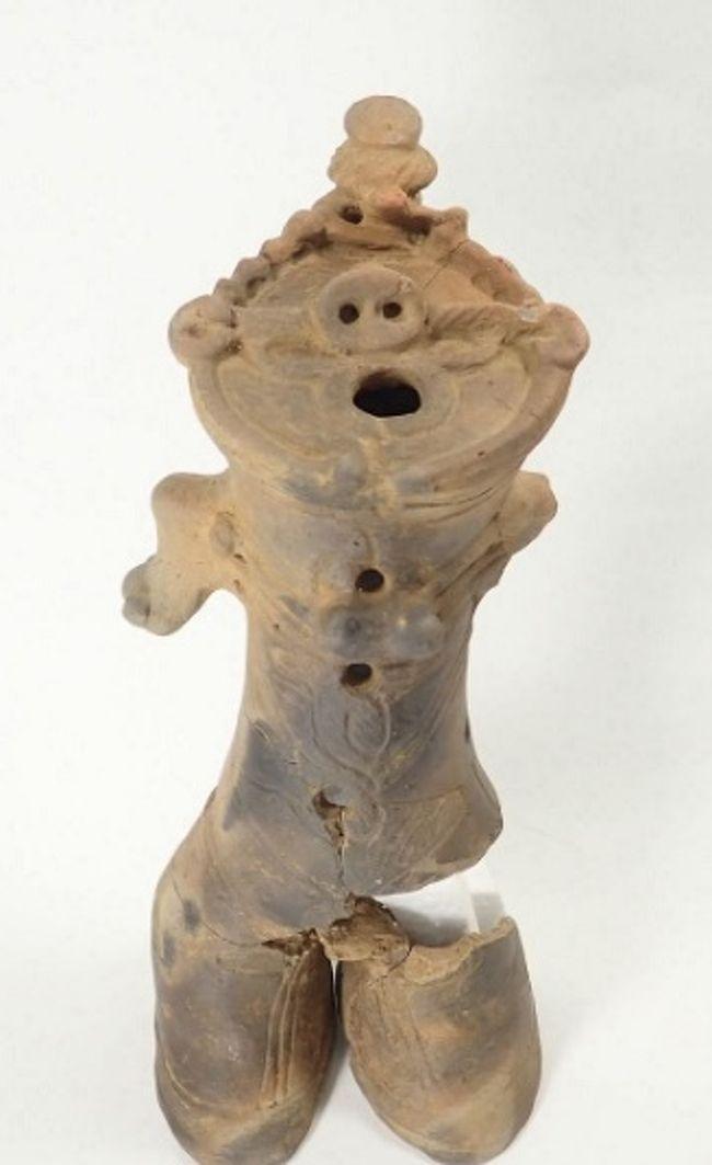 平成29年度調査青果展示会が横浜市歴史博物館で、「平成30年度発掘調査青果発表展示会」と銘打って7月3日(火)~7月8日(日)まで開催されている。分かり難いのだが、パンフレットには、「平成29年度に、(公財)かながわ考古学財団が発掘調査を実施した遺跡を、スライドなどを用いた発表や出土品の展示・解説で紹介します。」とある。要は、昨年度の発掘調査の成果を2F廊下に展示しているのだ。<br /> 菩提横手(ぼだいよこて)遺跡(秦野市)からの出土品は弥生時代や古墳時代のものが展示されている。しかし、この中には菩提横手遺跡から出土した「中空土偶」もある。これは縄文時代後期前葉~中葉(約3,500年前)の住居跡の覆土中から出土した。この中空土偶はずん胴で先が2つに分かれて2本の足になっている。ただし、左足は破損し、一部は失われている。性器も破損して失われているようだ。また、左手も欠損している。ずん胴の上は蓋で閉じ、2つの鼻穴を空けた豚鼻をしており、その下に丸く穴が開けられ口を現わしている。また、鼻の下、口の上にある左右に葉のように見えるのが目であろうか?全くのところ、顔の意匠が初めて目にするものだ。<br /> 鼻の上の頭に冠を擁いているようにも見えるが一部が破損しているのであろうか、非対称になっているとしたらこの冠の飾りであろう。実はこの中空土偶には横にも穴が開けられているが、右側は等間隔に穴が開けられているが、左側は等間隔ではなく、適当に穴を開けている。普通なら、この左右に開ける穴も左右対称とするのだがこれはどうしたことであろうか?土偶製作者がまだ製作に手馴れていないようにも思える。そのために、不思議な顔立ちとなり、出土場所も墓などではなく住居跡なのであろうか?<br />(表紙写真は中空土偶)