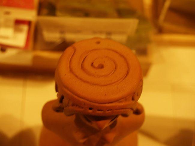 横浜市博物館に行ったついでにミュジアムショップを覗いてみた。土偶関係の本が並んでおり、昨年に初版が発行され、今年になって第2版か第2刷が発行されている本も2冊も並んでいる。最近は土偶ブームで研究者がいるのだろうかと見てみると、著者名に「譽田亜紀子(こんだあきこ)」とある書もある。「土偶女子」ということで、考古学の縄文時代を専門とする博士などの研究者ではない。こうした「土偶女子」が山川出版などの歴史書専門の出版社から本を出しているので驚いてしまった。<br /> こうしたミュジアムショップには土偶のミニチュアや埴輪のミニチュアが並んでいるのが普通である。ここのミュジアムショップでは「縄文のビーナス」と「仮面の女神」の国宝土偶のミニチュアが並んでいる。3種類あるが、いずれも「縄文のビーナス」と「仮面の女神」が同じ大きさにできている。一方は小型で他方は大型である。縮尺が全く異なることは仕方がないにせよ、「縄文のビーナス」は本物とは無関係のデザインに変更されている箇所があり、いくらお土産品であるとはいえ、こうした博物館のミュジアムショップで販売するのには問題があると思った。<br /> 1つは「縄文のビーナス」の被り物が未完のままで空洞であり、茶飲み茶碗を載せているようなデザインになっている。これを買った人は本物ではどうなっているかを調べるであろうし、調べるまではどうなっているのか想像もしようか。しかし、空洞にしなければならない理由が見当たらない。<br /> 他の1つはこの被り物のデザインが同心円状の模様に変更されている。どんな権利があってこのような変更ができるのか!<br /> もう1つは金銅か何かの金属製の高価なのもので、これは被り物のデザインを省略している。では何故省略してしまっているのか?そんなものを高額で売っているのは詐欺行為に近いのでは?疑問が湧く。<br /> かつで上野の東博のミュジアムショップで見た「縄文のビーナス」のミニチュアは本物と同じデザインで、被り物は「の」の字になっていた(https://4travel.jp/travelogue/10868218)。当時はここ横浜市博物館のミュジアムショップに並んでいる3社の製品は出ていなかっただけなのかも知れない。しかし、東博のミュジアムショップであれ、地方の博物館のミュジアムショップであれ、こうした本物とは異なる意匠に変更されたミニチュアは販売すべきではないと思う。どんな権利があって意匠を変更しているのであろうか?そうした行為は日本の歴史や文化を踏みにじる行為以外の何物でもないだろう。また、こうした「縄文のビーナス」や「仮面の女神」のミニチュアを販売目的で製作する際に、茅野市尖石縄文考古館からの承認は貰ってはいないのであろうか?<br /> 営利目的で本物の意匠を勝手に変更していることには腹が立つ。<br />(表紙写真は東博ミュージアムショップで見た「縄文のビーナス」の被り物の意匠)<br />