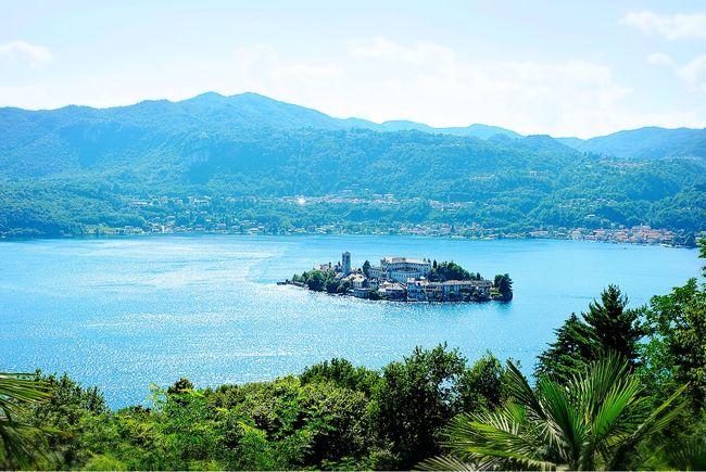 オルタ湖は、アルプスの山々に囲まれてたたずむ姿から「緑に包まれた小さな宝石」と呼ばれているそうです。そのオルタ湖に小さな島が浮かんでいます。それが『サン・ジュリオ島』。<br /><br />青い水をたたえた湖にサン・ジュリオ島が浮かんでいる景色。どこかで見た景色・・・そう、ちょうどスロベニアの『ブレッド湖』に似ているように思えました。<br /><br />オルタ湖の東岸から湖に突き出た岬の先端にオルタ・サン・ジュリオ(Orta San Giulio)があります。ピエモンテ州にある人口約1,300人の小さな町で「イタリアの最も美しい村」に認定されている町です。<br /><br />街の中心から歩いて15分ほど、高さ400メートルの丘を上ったところに、オルタ湖の『サクロ・モンテ』があります。そこはユネスコ世界遺産にも登録されていて、『サン・ジュリオ島』ともにオルタ・サン・ジュリオの見どころになっています。<br /><br />お昼頃、マッジョーレ湖のストレーザからタクシーに乗りおよそ40分ほどで、オルタ・サン・ジュリオの旧市街入口に到着。この日の午後から翌日の朝まで滞在し、イタリアの最も美しい村の一つを堪能しました。