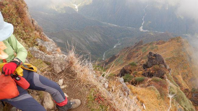 かつて「魔の山」と呼ばれた谷川岳。登山口となる上越線の土合駅前には谷川岳で犠牲となった5百余名の遭難者の名が刻まれた墓碑がある。途方もない犠牲者の数は日本一、いや世界一とも言われる。この「魔の山」も土合口からロープウェーとリフトを使って天神尾根からトマノ耳とオキノ耳の頂をめざすコースは多くの登山者が楽める安全な道である。10月9日、紅葉を楽しみながらこの天神尾根から双耳峰の2つの頂を目指した。<br />  ロープウェーの土合口駅は多くの登山者が列をなし、天神平から熊穴沢避難小屋、さらにその先の岩尾根の一帯は登山者の渋滞ができる状況だった。頂である「オキノ耳」から魔性の山を象徴する岳の東面、マチが沢や一の倉沢の紅葉を期待したが薄くガスで覆われており残念であった。
