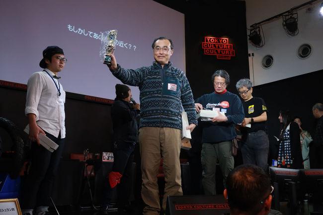 枻出版のBikeJINが主催する日本一周ラリー帳の企画は2018年で3回目。<br /> そして完走した人には、コンプリート賞としてトロフィーが授与されることになっているのですが、今年は完走者がたくさんでそうということで、トロフィーの発送費用を削減するために該当者は東京まで取りに来い、という仕掛けです。<br /><br /> おそらくトロフィーの制作費はスポンサー持ちで、発送費用は主催者持ちとなっているのだろう、なんてゲスの勘ぐりをしたりしますが、なかなか素晴らしい企画で東京まで行く価値あり、でした。<br /><br /> 1回目は完走50名、2回目は約80名だったのに対して今回は118名が完走したそうです。