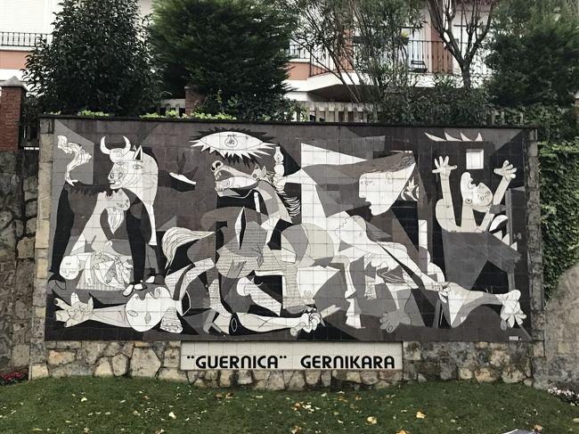 2017年12月11日の最後の見学訪問地はゲルニカです。<br />この町はスペイン内戦のおりに、後に独裁者となる反乱軍の指導者フランコ将軍の依頼を受けたナチスドイツ空軍が戦争の歴史上初めての都市部無差別爆撃を受けた。内戦時に共和国軍への兵站補給路の要だったので、フランコはここをぜひともたたきたかったのだそうです。ナチスドイツにとっても飛行機による爆撃や機銃掃射の絶好の実験場となったようです。ひどい話です。第二次世界大戦では都市部無差別爆撃は世界各地で枢軸国、連合国双方に多くの悲劇を生みましたが、その先駆けとなった。、<br />このゲルニカ無差別爆撃にショックと怒りを覚えた天才画家パブロ・ピカソがモノトーンの壁画「ゲルニカ」を亡命地のパリで爆撃の報を聞いてわずか数か月で描き上げた。あまりにも有名な絵ですね。<br />この町はバスク地方を構成するフランス領とスペイン領に広がる七つの地区のひとつビスカーヤ地区の政治的、宗教的な議事堂があり、議事堂の庭の「バスクの樹」と言われる樫の木のもとでカスティリャ王家から自治を認める式典が行われたのだそうです。いまでもビスカーヤの議会機能はこの町の議事堂で行われ、行政府としての都は、この町の訪問の前に行ってきたビルバオにあるのだそうです。<br />バスでビルバオから暗くなるちょっと前にこのゲルニカに到着し、議事堂と市庁舎の近くにある石板を使って作成されたピカソの「ゲルニカ」のレプリカの壁画を見学しました。そのあと少し自由時間で街歩きをしたのでした。<br />表紙はレプリカのゲルニカです。道端の土手の壁面にあります。