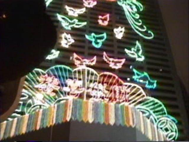 張曼玉(マギー・チャン)の『ラヴソング』が気に入ったので<br />映画と同じ旧正月大晦日にヴィクトリア・パークに行こう、<br />と言うのが一番の目的…<br /><br />(だと思っていて) 書きだしたのだが…<br />調べると映画の日本公開は 1年後の 98年2月7日、<br />僕が見たのは2月20日 渋谷のシネセゾン!!<br />つまり、きっかけは映画ではなく、単に<br />香港の春節を見たいと思って来たようだ。<br />でもまあ、映画と同じようにパークで雨に遭ったし、<br />映画を見て、ここだ!と強い印象を持ったはずで、<br />都合のいい記憶の修正もムリないよね (??)<br />ちなみに返還まで半年を切っているが、少なくとも<br />鈍感な異邦人の旅行者には特に何も感じられなかった。<br />(香港は 80、82、95、97年と4回目)<br /><br />写真はヴィクトリア・パークのそば、<br />パーク・レーン隣の Winsor House です。<br />商売人の街 香港らしい &quot;恭喜發財&quot; のネオンが。<br />そう言えば『ラヴソング』でも新年の挨拶を<br />何種類も言い合うシーンがあったな…