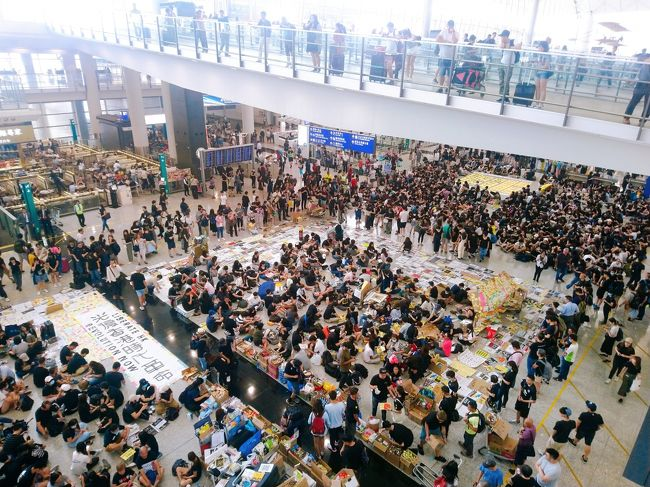 香港大丈夫?という連絡をあちこちからいただきましたので、先日利用した香港国際空港での大規模集会の様子、と、欠航情報について、書いておきたいと思います。<br /><br />あらかじめ予定されていた通り、香港国際空港では、8/9の13時から3日間の予定で大規模集会が行われていました。本来であれば、8/11に集会は終了する予定でしたが、8/11に尖沙咀の警署外で起きた女性の右目負傷事件(警察が女性の目に向けてビーンバッグ弾を打った事件。一部報道では右目を失明したともいわれているほど重傷)で、その翌日の8/12、さらに多くの抗議者が空港に訪れ抗議をしました。そのため、8/12の夕方、香港空港のすべての発着便が欠航となりました。<br /><br />航空会社は本日8/13の午前6時から対応を始めていますが、いまだほとんどのフライトが欠航している状態です。詳しくは香港国際空港の発着情報か、航空会社にお問い合わせください。<br /><br />別ブログでもまとめましたので、ご参考までに<br />https://www.travelhongkongmacau.com/entry/hkprotest0813<br /><br /><<以上8/13の香港現地時間午前8時の時点での情報です。>><br /><br /><<以下8/13の香港現地時間午後6時半の時点での追加情報です。>><br /><br />本日も13時より空港で抗議集会が開かれ、抗議者が禁止区域の入口にカートを置くなどしたため、16時よりチェックインを一時停止していましたが、17時すぎに本日のフライトの全便欠航が発表されました。<br /><br /><<以下8/14の香港現地時間午前7時の時点での追加情報です。>><br /> <br />本日(8/14)は朝からフライトの運行が再開しています。まだ少しですが欠航便もあるようですので、香港空港の発着情報を確認してから空港に向かうようにしてください。<br /><br />なお、現時点ではまだエアポートエクスプレスのインタウンチェックインは利用できない模様です。