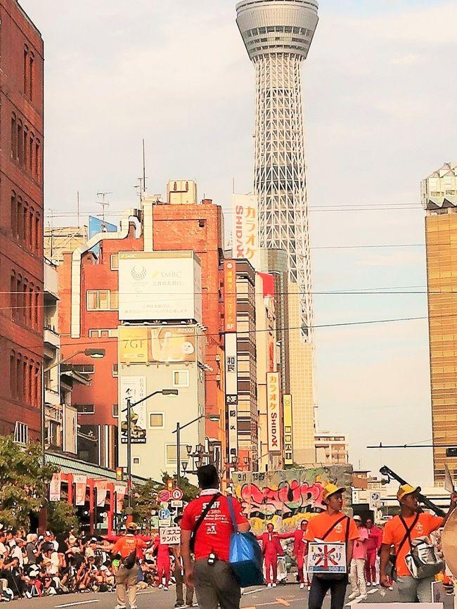 行く夏を惜しんで 浅草サンバカーニバル 東京中日スポーツ  2019年9月1日 朝刊<br /><br /> 北半球最大のサンバの祭典「浅草サンバカーニバル」が8月31日、東京都台東区の浅草寺周辺であった。華麗なダンサーらが息の合ったステップを披露し、観客を魅了した。<br /> パレードコンテストには、二つのリーグに計16チームが出場。各チームが「忍者」や「チョコレート」などのテーマを設け、800メートルのコースを40分かけて思い思いに踊り歩いた。最高峰のS1(1部)リーグでは、地元・浅草の「仲見世バルバロス」が優勝し、4連覇を達成した。ほかに、地元小学生のサンバチームなども参加した。<br /> 浅草サンバカーニバルは38回目で、地元の人たちでつくる実行委員会の主催。毎年50万人が訪れる。<br />https://www.tokyo-np.co.jp/article/national/list/201909/CK2019090102000126.html#print より引用<br /> <br />浅草サンバカーニバル(Asakusa Samba Carnival)は、東京都台東区浅草で行われるサンバのパレード及びコンテストである。第1回は1981年に行われて今日まで続いている。日本で最大のサンバカーニバルのコンテストとして知られる。 <br />浅草サンバカーニバル実行委員会による主催で、毎年8月の最終土曜日に開催される。約50万人の人出がある。 <br /><br />各サンバチームの規模に応じてリーグ制によるグループ分けがなされている。出場順から、地域のブラスバンドなどによるコミュニケーションリーグ、企業チームによるテーマ・サンバリーグ、S2リーグ、S1リーグの4つのリーグに分けられている。このうち、S1とS2リーグではパレードの内容をコンテストで競う。 <br /><br />S1及びS2リーグでは、リオのカーニバルになぞらえて、パレードの内容を審査員や沿道の観客によるモバイル投票などの採点方式により順位や優勝が競われる。<br /><br />特にトップリーグであるS1リーグでは、エスコーラ・ジ・サンバ(略称:エスコーラ)といわれる大規模なチームによって順位が競われる。これら大規模なチームは、カーホ・アレゴリア(略称:アレゴリア)といわれる大がかりな山車を製作したり、ファンタジアと呼ばれる衣装をブラジルに発注製作したものを使用するなど、大規模に展開するチームが年々多くなっている。 <br /><br />S1リーグにおいては、アレゴリアの製作が参加必須条件となっている一方、S2リーグではアレゴリアの導入は禁止されている。 <br />そもそもサンバには様々なスタイルがあり、ヂスフィーレと呼ばれるパレード・行進するサンバは「動くオペラ」とも評される。これは毎年、各チームがEnredo(エンヘード。物語やテーマなどの意)を決め、それに基づいた楽曲や衣装、山車を製作し、それをパレードによって表現し、審査によるコンテスト形式で順位を競うからである。 <br /><br />このように、近年の浅草におけるサンバカーニバルでは、S1リーグに出場するチームを中心に本格化させようとする傾向が強くなっている。 <br />サンバにおけるパレードは、毎年チームで検討し選んだエンヘードのテーマが優れているか、またそれをいかに全体で表現するかを各チームで競うものである。またサンバパレードと言えば、露出度の高いダンサーが多いと誤解されているが、これも一部に過ぎない。タンガを着て踊るダンサーはパシスタやジスタッキ・ヂ・シャウン、ハイーニャなどと呼ばれるが、これらは少数のパートであり、一つのチームの中には、アーラといわれるパートのグループ分けがいくつもあり、ダンスやパフォーマンスなどいろいろな役割を演じるのが特徴である。 <br />(フリー百科事典『ウィキペディア(Wikipedia)』より引用)<br />