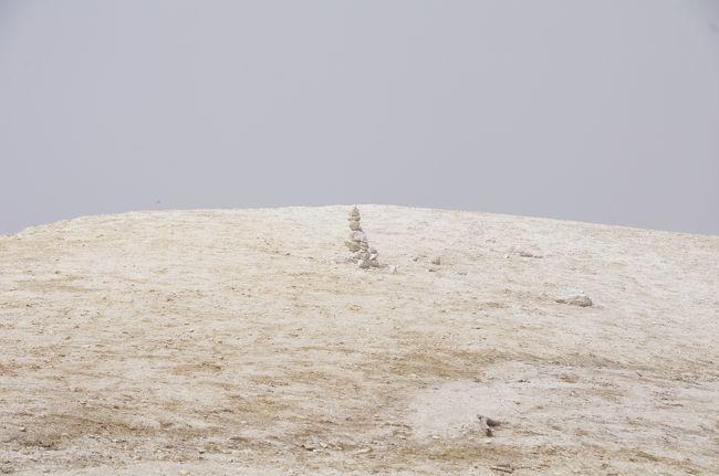 9月7日(土)、同僚との登山で山梨県北杜市の日向山(ひなたやま)を登りました。レンタカーに同乗し、標高約780mの尾白川(おじらがわ)の駐車場まで走りました。ここは日向山と甲斐駒ヶ岳の登山口であり、駐車場は混雑していました。若干雲が有りましたが、概ね良い天気でした。<br />9時40分頃の遅い登山開始であり、私達は8人でした。序盤から急な登りで、南アルプスらしいな。私は荷物をちょっとだけ重くしていました。他のメンバーは若い人ばかりで、やや速くて、ハアハア言いながら登りました。Tシャツ1枚でしたが、暑くて、滝汗となり、汗が目に染みました。途中、林道を通りました。ここから登山道に号目を示す標識が設けられています。「10/3」というような表記であり、なんだか分数が逆になっています。登りが続く道ですが、道はよく整備されており、危険は感じませんでした。他の登山客と頻繁に行き交いました。<br />緩やかになった頃、分岐が有り、一方の道を進み、すぐに三角点に着きました。1659.9mだそうです。分岐に戻り、頂上への緩やかな道を歩きました。<br />いよいよ頂上です。最初、目の前がガス(霧)で真っ白でしたが、すぐに視界が晴れました。花崗岩の風化した砂地の頂上です。眺望は雲のせいでイマイチでした。<br />見方を工夫しても、ビーチには見えません。ま、山です。ここでランチとしました。頂上はどこも傾斜が有り、平坦な所は有りませんでした。私はプリムスのバーナーとスキレットでおにぎりを焼きました。<br />食べ始めた頃、北側が晴れて、落ち着かないランチでした。山麓が綺麗に見晴らせて、八ヶ岳の素晴らしい景色となりました。八ヶ岳から続く蓼科山や霧ヶ峰もよく見えました。サントリーの白州醸造所がすぐ近くに見えましたが、そっちには下れません。近いはずの甲斐駒ヶ岳は見えませんでした。<br />荷物が砂まみれになり、カメラにも砂が付いて、心配になりました。メンバーの1人は裸足になっていました。標高1600mだそうですが、頂上の標識3つのいずれも壊れていました。<br />ここから、登った道を下りました。下りも速かった。