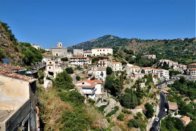 素敵な村、素晴らしいパノラマ、美しいビーチ、美味しいグルメをたっぷりと楽しんできました♪<br /><br />☆Vol.569:第19日目(7月4日)サヴォーカSavoca(メッシーナ県)♪<br />サヴォーカは標高330メートルの山上の村でメッシーナ県に入る。<br />イタリア美しき村に選ばれ、また、コッポラ監督のゴッドファーザーのロケ地として有名。<br />村の入り口にあたるVia Sant&#39;Onofrioの脇に展望広場。<br />その広場にコッポラ監督を模ったミラーの像が飾られている。<br />土産屋の前に小さな三輪車がある。<br />本当の目的地は婚礼を上げた教会へ行くこと。<br />かなりの山道なのでこの三輪車を借りて乗っていくことに。<br />細い急な傾斜のサン・ミケーレ通りを三輪車が猛スピードで走る。<br />次第に標高が高くなり、<br />周囲のパノラマは素晴らしい。<br />素朴な村の景観もまた素敵。<br />遠くに教会が見えてくる。<br />Chiesa di San Nicolo。<br />この教会は若きマフィアの婚礼が行われた場所。<br />その周囲は展望広場となっていて、<br />サヴォーカの全貌、美しい山々や青いイオニア海が広がる。<br />コッポラ監督が愛したこのひなびた風景は素晴らしい。<br />ゆったりと歩いて眺めて♪