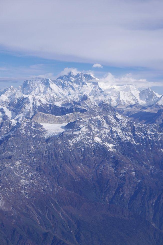 今回はヒマラヤ遊覧飛行で現物のヒマラヤ山脈を観るのが主目的です。<br />特に登山をするわけでもなく山にはそれほど興味がありませんが実物(エベレストとかマナスル)を観ることに意義を感じた次第です。<br />旅行中に遊覧飛行は「エベレスト遊覧飛行」と「アンナプルナ遊覧飛行」の2回あり、飛行機嫌いの私にはとても苦痛でした。それも危険な中型のプロペラ機での飛行です。<br />これらの遊覧飛行は天候に左右され飛行機が飛ばなかったり、飛んでも何も見えず引き返すことが多いそうですが今回は幸運にも2回とも良好に観光出来ました。<br />席は左右窓側の一列のみで左右の席の搭乗者に公平な観光が出来るように山の上空で旋回してくれます。<br />また搭乗席の窓は汚れて汚く鮮明な写真を撮れるように操縦席に順番に入れてもらえます。<br />ただ標高の高い山々は多くてどれがどの山か説明されてもさっぱり分からなかった。<br />また2015年4月25日のM7.8の大地震による被害でカトマンズ市内の建物等は修復工事中のものが多かった。<br /><br />ネパールへは羽田からタイ国際航空のTG-661便(深夜発)でバンコック経由でカトマンズへ向かいました。<br />バンコックでの乗り換え時間は5時間近くありラウンジにでも入らないと時間を持て余します。<br />バンコックの空港は全面禁煙なのでタバコを吸うことは出来ません。<br />バンコックの空港(国際線)はラウンジ(PRIORITY PASSで入れる)の数が多くとても便利です。<br />特に「シューマイ」が美味しいのですが置いていないラウンジもあります。<br />然し国内線のターミナルは航空会社のラウンジ(ファーストクラス、ビジネスクラスや上級メンバー用)しかないので大違いです。<br /><br />ネパールの時差は3時間15分あります。<br />ネパールは土曜日が「休日」で日曜日は平日と同じで学校や銀行もやっています。買い物をする場合、土曜日は閉まっている商店が多いので避けた方がいいです。<br />通貨はネパールルピーで日本円とほぼ同額なので分かり易い。<br />現地ガイドは5,000円を5,000ルピーで両替していた。<br />私は今回も両替はしなかった。米ドルが通用する店もあった。<br />現地ガイドが付き添っていたのでドルの使えない店舗では1,000円単位でルピーに両替してもらった。<br />有料のトイレは20ルピー(20円)です。<br />トイレの間隔の短い人は少額を両替しておいた方が良いです。<br />Y-モバイルの携帯電話もローミングサービスが使用出来ます。<br />私は携帯電話を「目覚まし時計」替わりに使用するのでローミングサービスが使用できると時差調整が不要になるからとても助かります。<br /><br />現地のタバコは日本に比べて格安です。50~250円くらいです。<br />喫煙者は羽田や成田の免税店(280~300円)で購入するよりも現地で購入するのが得策です。然し好みのタバコがあるかどうかは保証できません。ネパールの「PILOT」(標準よりも少し短めでフィルター付き)と云う100円のタバコは私好みで美味しいと思った。<br />日本のタバコの「エコー」の様な味です。<br />ネパールの平均月収は35,000円くらいなので現地の人たちにとっては高額のようです。<br />自動車は右ハンドルで通行方法も日本と同じです。<br />オートバイは殆どインドと同じだった。<br />運転者はヘルメットを着用しているが同乗者は大体ノーヘルです。<br />街並みはインドよりも多少はましな気がしますが良く似ている。<br />食べ物もほぼインドと同様でカレー風味のものが多い。<br />この時季の気候はほぼ日本と同様で過ごし易かった。<br />街は埃っぽいところが多かった。<br />ウシは「水牛」以外は食べないので「ケンタッキーフライドチキン」の店はあるが「マクドナルド」は一軒もない。<br />「水牛」は食用にも使役にも使えるとのこと。<br />山中のホテルを除いてWiFiは設置されている。<br /><br />現地のガイドは「お釈迦様」はインド人ではなくネパール人であることをしきりに強調していた。<br /><br />寺院の近くでは「仔ヤギ」を見掛けることが多い。これは「生贄用」のヤギで喉を切って神仏に供えるそうで寺院の石畳みには生贄にされたヤギの血が点々とこびり付いていた。<br />生贄にされたヤギは専門に解体する店があり食肉用に捌いてくれるのでそれを持ち帰るそうです。<br />私もヤギカレーを食べたが美味しかった。<br /