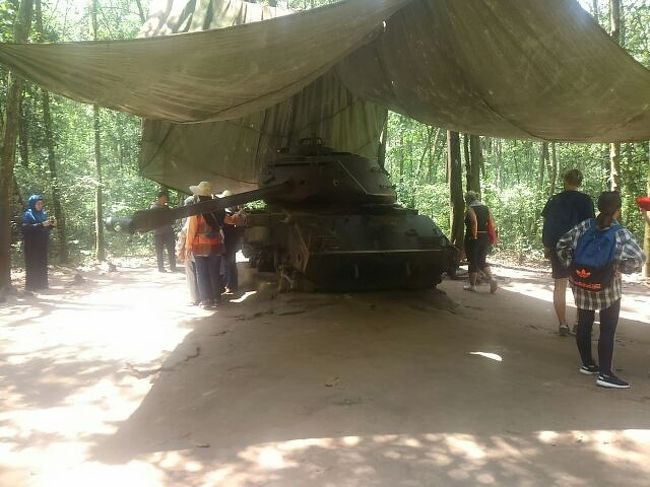 Cuchiの司令部跡は今は林に覆われているが、ベトナム戦争時にはどうだったのかは分からない。枯葉剤で丸裸にされていたかも知れないが、今は自然の林、ジャングルとまでは言えないが、密生した雑木林になっている。ここに北ベトナム正規軍が集結し、トンネル内に息を潜め、機を見て抜け出し、米軍、南ベトナム正規軍を悩ました。所謂ベトコン、Viet Nam コンサン(共産)のことだ。北のベトナムにより、南は所謂開放され、今この国は共産国家になっている。中国、ベトナム、ラオスが共産国家だが、旅行者がこれ等の国を旅行する限りでは、共産国家だからといって大きな不便は感じないが、しかし、最近の中国では一般旅行者が明確な理由もなく、突然に逮捕、勾留される事例が頻発していて、安心できない。共産国家の怖さもある。<br /><br />そうした林の中に集会テント、タンク、貯蔵穴、調理場、簡易医療施設などもあって、一つの組織的な機能を果たしていた。映画プラトーンでは米軍がナパーム弾を投下し、林の中でベトコンと米軍の銃撃戦が行われ、重武装ヘリが上空から銃撃し、危機に瀕した兵員を救出する。林の中を歩き、そんな映画の1シーンなども想像できた。トンネル作戦と言えば、日本軍はこれを塹壕戦術と言って、その最たるものは、栗林中将率いる硫黄島防衛軍で、島の北部、摺鉢山の中をハリネズミのように穴を張りめぐらし、艦砲射撃にもよく耐え、上陸してきた米軍に対し、縦横無尽の戦いを挑み、結果は矢弾尽きてほぼ玉砕したのだが、太平洋戦争中では米軍に最大の人的被害を与えた戦史に残る攻防戦だった。ベトコンはこの硫黄島攻防戦、或いはフランスマジノラインの塹壕を参考にし、圧倒的相手方戦力に対抗する為にトンネルの有用性に思い至ったものだった。そして遂には強敵米軍に打ち勝ったのだった。<br /><br />林の一番奥に射撃場があり、射撃をする客の為に30分の休み時間があるが、かなり歩いてきたので、ここで一休みするのはありがたい。ビールを頼んだら、キオスクのおばちゃん、日本語で「40ドン」と言ってくる。自分の顔に日本人との印は付いていないのだが、どうして直ぐにも日本人と分かるのか、不思議でしょうがない。売店でお土産のベトコン帽を買って、さて、これからU-ターンして、帰りのジャングル遊歩道を歩き、元の入り口に向かった。