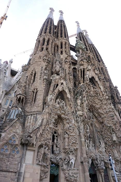 「サグラダ・ファミリア(聖家族教会)」<br /><br />サグラダ・ファミリアは史上最も偉大な建築家アントニ・ガウディの作品群の一つとして世界遺産に登録されています。 <br />1882年に着工、翌1883年から当時まだ無名だったガウディが引き継ぎ、着工から130年以上 経った今も建設が続いています。 <br /><br />実際にガウディが生前に完成させたのは「誕生のファサード」のみです。<br />全体の建築としても特徴的で美しいですが、ガウディによる「誕生のファサード」はよく造ったものだと思える異彩を放っています。<br /><br />ガウディの没後(1926年に没)100週年にあたる2026年には完成するとされています。 <br />日本人彫刻家・外尾悦郎さんの作品も数々あります。