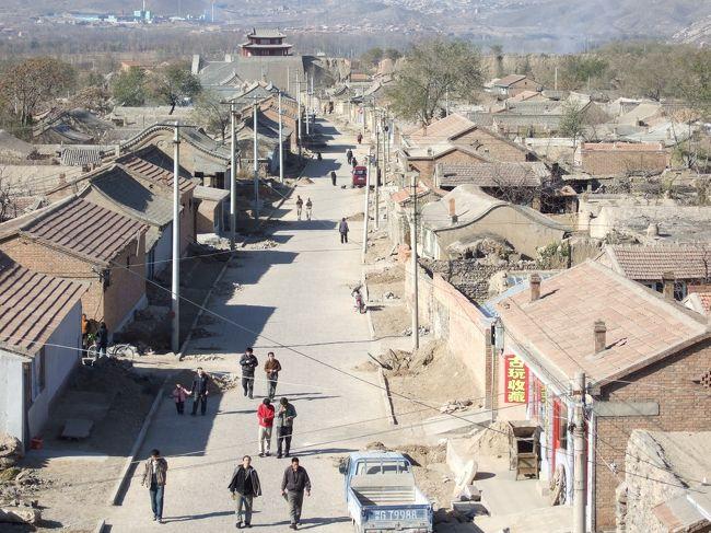 河北省鶏鳴古城は北京から150キロ、車で3時間のところにある。<br />別名、鶏鳴驛といい、1219年にチンギスハーンが作った宿場だそうだ。約2キロに及ぶ城壁で囲まれており、住民は1,000人程度の小さな村だ。<br />1998年公開の松竹映画「てなもんや商社」(本木克英監督のデビュー作品)のロケ地でもあるが、そのことを知っている人はまずいないだろう。ほんの数シーンの撮影だったので、スタッフは車で現場に連れて行かれただけで、そこがどこかも分からない者が大半だったと思う。小さな作品だったがディテールまでしっかりアイデアの練られた、実に面白い作品だった。主役の小林聡美や渡辺謙の好演も見応えがあった。中国のこんな辺鄙な片田舎での撮影は、不便極まりなかったに違いない。<br />そして2007年、僕は仕事絡みで、この村を視察することになった。<br />100元で村の案内人を雇う。普段は野良仕事をしているに違いない真っ黒に日焼けしたおじさんだ。<br />さて、この鶏鳴古城にはひとつだけ歴史的な大事件があった。1900年の義和団事件で、八カ国連合軍に攻め入れられた西太后と光緒帝は、紫禁城を追われて西安に逃げた。その道中、西太后ご一行様がこの宿場に一泊したのだ。<br />あのおじさんが、どや顔で<br />「オラの村さ、あの西太后さまがお泊りになったべ」<br />と話していたのが印象的だった。<br />