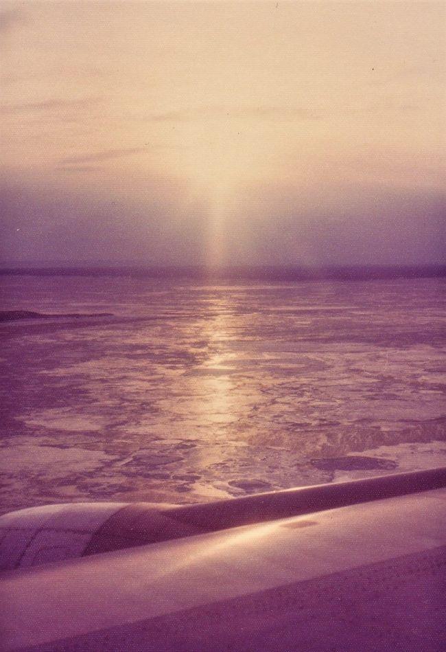 古い写真をスキャンする旅のシリーズの続き。これは私の初の海外の旅で、長年の憧れであったヨーロッパを、1974年12月19日福岡空港発、羽田空港乗り継ぎのJALで出発したつ。どちらもジャンボ・ジェット機だった。羽田空港からアラスカのアンカレッジ空港まで行き、給油のため途中降機。それからパリまで行く予定の日本航空便だったのだが、確か乗務員ストのため、デンマークのコペンハーゲン空港までしか飛べないといういきなりのハプニングだった。(当時パイロットはお雇い外国人が多かったはずだ。)    <br /><br />期せずして、行く予定のなかったデンマークのコペンハーゲン空港でチェックアウトして近辺を歩いた。これが私の初のヨーロッパでの第一歩となった。12月20日朝10時ごろのことだ。日本航空の飛行機はパリまで飛ばず、結局、SASスカンジナビア航空に乗り継いで、パリのル・ブールジェ空港に到着することになった。<br /><br />帰国時は、1975年1月10日ローマ空港発のフライトで、日本航空のジャンボ機ではなく、古いDC8か古いボーイングだった。エンジン音がうるさかったのを覚えている。チャーター機利用で少し安くなったせいかもしれない。当時は行きと同じで、北極海経由でアラスカ上空を通過しアンカレッジ空港で給油した。1月11日に羽田空港到着だった。<br /><br />一枚目は帰国便で、アンカレッジ空港着陸直前の撮影。氷海が見える。真冬だから、太陽はこれでも高い位置に来ているのだろう。<br />(2020年9月19日記す)