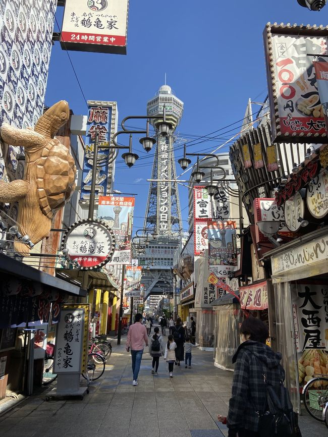 大阪の象徴とも言える通天閣に初めて登ってみました。<br />大阪メトロの御堂筋線で動物園前駅より徒歩5.6分ほどのところにありました。<br />駅を降りると大阪の下町というような独特な世界観。<br />通天閣に続くメイン通りはたくさんの串カツ屋さんが並んでいて、残念ながら閉店してしまったフグ料理で有名な<br />づぼらやさんもありました。<br />ちょうどづぼらやさんの前あたりが、賑やかな街並みと通天閣を見渡せる1番いい写真スポットでした。<br />通天閣へ登るには一度地下の券売所まで行きチケットを買います。<br />3歳までは無料、5歳以上は400円、大人は800円です。<br />チケットを買ってすぐにエレベーターで上の階にあがって行き、5階の黄金の展望台に到着です。<br />この日はとても晴れていて大阪の街並みが一望出来ました。<br />通天閣といえば足を撫でるとご利益があると言われているビリケンさんがいますが、コロナ渦の為エアータッチでお願いしますと張り紙がありました。<br />ちなみにもう一つ上の階にある特別展望台はまた別料金で500円かかります。5歳以下の子供は登れません。<br />展望台以外にも展示物がたくさんあり、お土産屋さんもあり楽しかったので大阪に遊びに行ったらまた行きたいなと思います。
