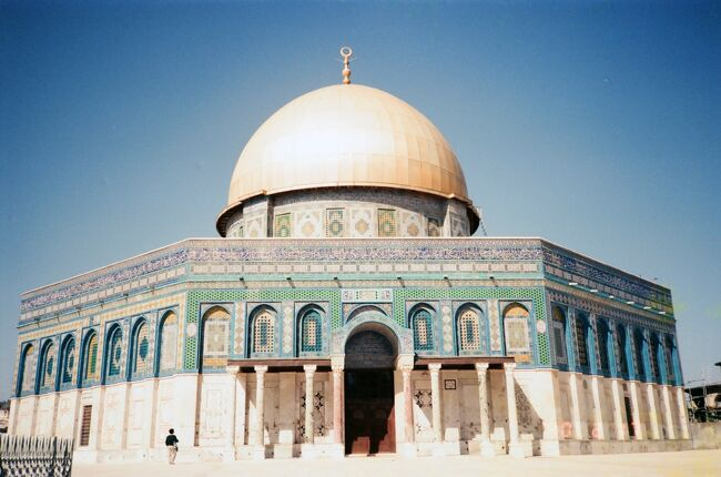 トルコ、シリア、ヨルダンと巡って、次に向かったのがイスラエルのエルサレム。ユダヤの都で約束の地とされた場所。イエスが十字架に架けられたところ。ムハンマドが昇天したイスラム第3の聖地。3つの一神教を育んだ地であり、宗教的的な争いが絶えないところです。1990年のこの頃、東エルサレムを含むイスラエルの占領地では「インティファーダ」というパレスチナの抵抗運動が行われていました。欧米からの多くの巡礼者が訪れ、一軒平和なエルサレムの旧市街では、アラブ人地区の商店ではお昼を過ぎると一斉に商店が店を閉めていました。インティファーダの一環だったのでしょう。<br /> 日が暮れると、10代後半から20代前半の当時の私たちと同世代の若い兵士たち(イスラエルは女性も含め、皆兵制です)がライフルを手に通りを巡回しています。アラブ系、パレスチナ人の人たちが夜遅く、通りを歩くことはほとんどありません。こんな時間、通りを歩くのは旅行者、それも旧市街の安宿に泊まっているような若いバックパッカーたち。旅先で知り合った仲間の宿へ、決まったルートを歩いて行く。その道すがらに会う兵士たちはいつも同じ顔ぶれ。自然とすれ違うたびに「ハーイ」とか、声を交わすようになる。そこにいるのは自分と変わらない人たち。でも、彼らは命令があれば、持っている銃で人々を傷つけるかもしれない。<br /> 数千年の歴史に翻弄され続けてきたエルサレムでは多くの旅仲間と出会うことができました。夜遅くまでとりとめのない話をしたのも良い思い出です。一方で占領する側とされる側、ほんのわずかですが、その現実を肌感覚で体験できたのは貴重な経験でした