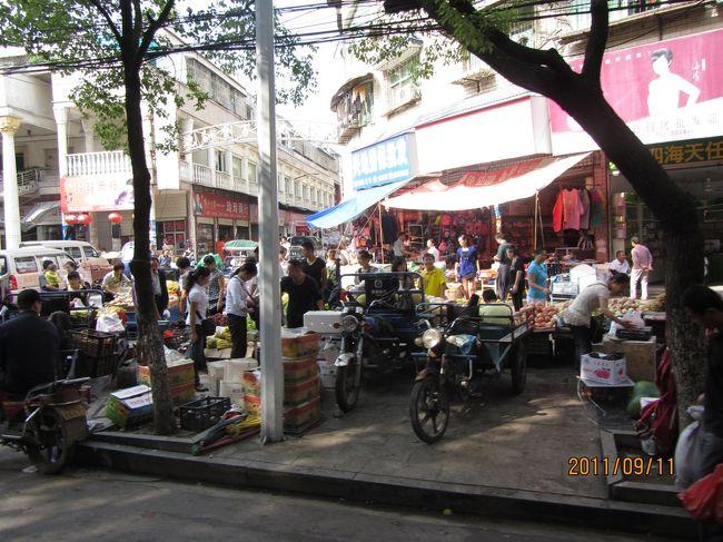 赤壁市内の商店街・市場の風景です。<br />歩道いっぱいに 露店が並びます