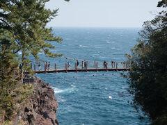 門脇灯台パーキングに着いたのが午後1時頃。先にこの先の「ぼら納屋」まで歩き昼食を済ませ、腹ごなしに海岸線を歩いてここに戻るようにした。 駐車場脇の展望所のようなところから目の前に吊り橋が見られるようになっていた。 濃い海の青が印象的。ただ風が強いので穏やかな海というわけにはいかない。