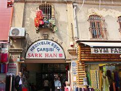 """私が探していたのは、キャラバン・サライの付属施設であるハン。 キャラバン・サライとは """"隊商の宮殿""""を意味するトルコ語で、オスマン・トルコ時代に街道を往くキャラバンや旅人に提供されていた無料の宿を指す。  そして、大きな町のキャラバン・サライには、ハンと呼ばれる商業施設が付属して建てられていた。 ハンとはもともとは大規模なキャラバン・サライのことであったのだが、利用されていく内に宿泊施設としてだけではなく商業施設としても発達した場所で、通常は二階建て以上の中庭を持つ構造であり、一階が倉庫、二階と三階には個室の部屋があり、宿泊場所やその地方の営業所としても借りることが出来た…と云う建物だ。  旅の前に旅行記を読んでいて、オスマン・トルコ時代のハンの建物がイスタンブールの港沿いの地区にはまだ残っている…という事を知った。 そして、そのハンがあるらしいのは、エジプシャン・バザールのある地域の高台のあたり。  地図も、案内書も何もない。 だから、とりあえず歩いて探すしかない。  そして、道沿いにHANと名前の書かれた建物を発見! SARK HANと書いてある。 建物の二階部分を見上げると、多分、個室の窓だと思わせる様な雰囲気だ。  やった〜!見つけた!"""