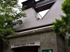 〔 サントリー ウイスキー博物館 〕  しばらく森の中を進んでゆくと、屋根の形が特徴的な「サントリー ウイスキー博物館」へと到着。  ここがツアーの集合場所になっているのですが、開始の13時30分までしばらく時間が空いているので、先に博物館内を見学し予習しておきましょう。