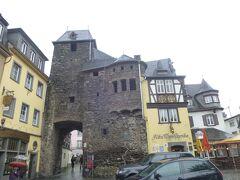雨の中、最初に600年以上の歴史を誇るワイン酒場であるAlte Thorschenkeアルテ トルシェンケに行く。  町を守る要塞の一部、つまり17世紀末、仏軍に焼かれて黒くなったと思われる城壁とEnderttorエンデルト門に連結した建物は薄い黄土色の壁、木組みの家(ホテル兼酒場)だ。  1970年代の古城ホテルの加盟リストにあったので、昔からよく知っているが、宿泊・食事をしたことは無い。雨宿りを兼ねた客も多く、そこから離れた。  参考;Alte Thorschenke古城ホテル アルテ トルシェンケ D-56812 Cochem 、Brueckenstrasse 3  http://www.alte-thorschenke.de/restaurant.htm ホテル&レストラン アルテ トルシェンケ  3星・全35室。モーゼル・コッヘムの600年以上の歴史を語るホテル・ワイン酒場である。 アルテ トルシェンケはドイツの最も有名なワイン酒場である。トリアーの選帝侯バルトウィン(ルクセンブルク伯)が1332 年に町を守る要塞を建てた時の一部にあたる。 当初、城壁看守や兵たちの住居に利用されていた。また、ケルンやフランクフルト間との郵便馬もここが起点になっていた。 その後、アルテ トルシェンケの美味しい料理やワインが有名になり、時代とともに、魅力は増し、画家たちはロマンチックなアルテ トルシェンケを描き、詩人は同様にアルテ トルシェンケを詩歌で称揚した。アルテ トルシェンケの歴史は町や古城と共に生きてきた。 アルテ トルシェンケはコッヘムの家並みを語る上で欠かせぬものであり、誰もが旅での最も気に入りの写真として、このアルテ トルシェンケを撮っている。 (番外参照:伝説エンデルト門)  写真は伝説エンデルト門とアルテ トルシェンケ  モーゼル・コッヘムの伝説・エンデルト門とワイン樽 http://4travel.jp/travelogue/11236579