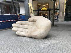 おおっ、これですねブラボーが投げたアンティゴンの手は。聖母大聖堂裏手のマルクト広場にあるブラボーの像がまさにもぎ取った巨人の手を投げる姿で、これがその手とされています。みんな手のひらに寄りかかって写真を撮っていましたよ。