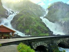 この日ドライブしたハダンゲルフィヨルドからリーセフィヨルドまでの道は、滝街道とも呼ばれる道で、氷河が削った山肌からは雪解け水が迸る幾筋もの滝が勇壮な姿を見せてくれる。  この写真の滝も滝街道にあるそんな滝の一つ;Latefossen(ラテフォッセン:ラテ滝)で、水量も多い7月は車道の上にもその水が跳ねてマイナスイオン大放出中。 車の外に出ると、あっという間に体は滝のミストで被膜されてしまった。  この日の朝はプレーケストーレンへの道を急いでいたので滝の展望台では車を止めずに通り過ぎるだけとしたのだが、Latefossenをはじめとするハダンゲルフィヨルドの絶景ドライブ・ルートについては別旅行記(旅行記2)で改めて紹介したいと思う。