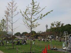 天王寺公園内のテンシバと呼ばれる芝生のある場所では人々が寛いでいる。向こうに通天閣が見える。通天閣までは1km少しだ。